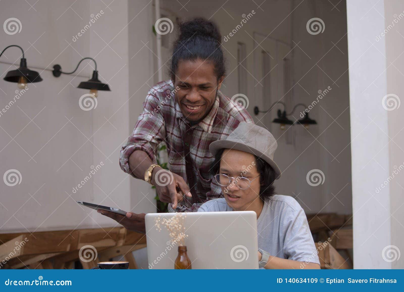 Το νέο δημιουργικό άτομο δύο συζητά με το lap-top και την ταμπλέτα, νέους Ασιάτη και το μαύρο που λειτουργούν με την ταμπλέτα και