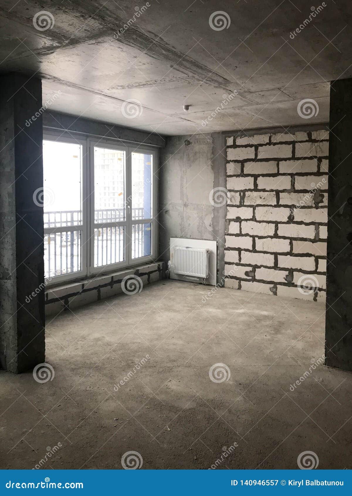 Το διαμέρισμα στο νέο κτήριο με ένα ελεύθερο σχεδιάγραμμα χωρίς επισκευή και τη διακόσμηση με τους γυμνούς τοίχους ένα μεγάλο παν