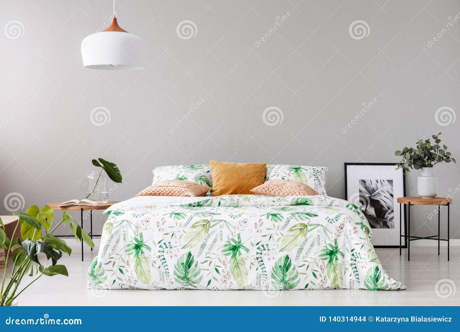 Το διπλό κρεβάτι με το floral duvet και το ροδάκινο χρωμάτισε το μαξιλάρι μεταξύ δύο ξύλινων nightstands με τα λουλούδια στα βάζα