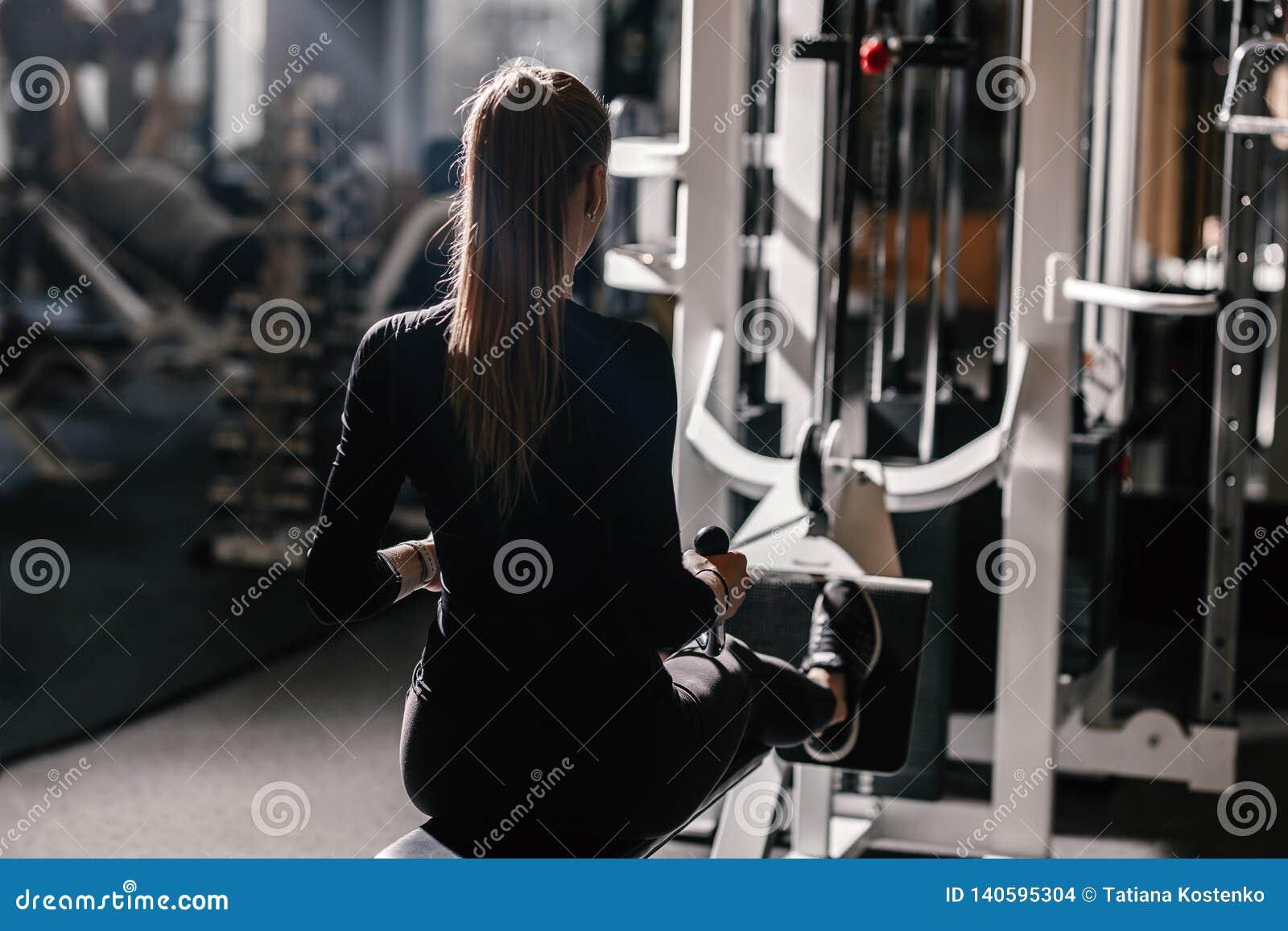 Το όμορφο αθλητικό κορίτσι που ντύνεται που ντύνεται μαύρο sportswear κάνει τις αθλητικές ασκήσεις με τον εξοπλισμό στον πάγκο