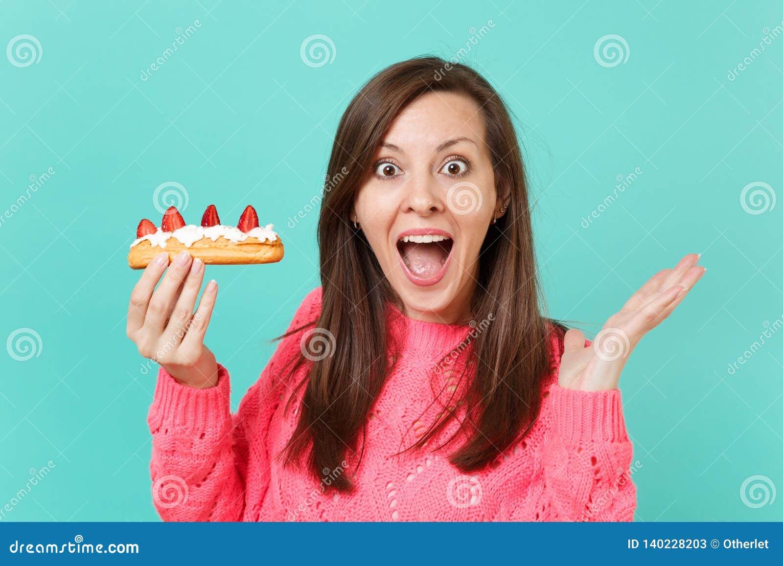 Το συγκινημένο νέο κορίτσι στο πλεκτό ρόδινο πουλόβερ που κρατά το στοματικό ευρύ ανοικτό κοίταγμα εξέπληξε το διαθέσιμο κέικ ECL
