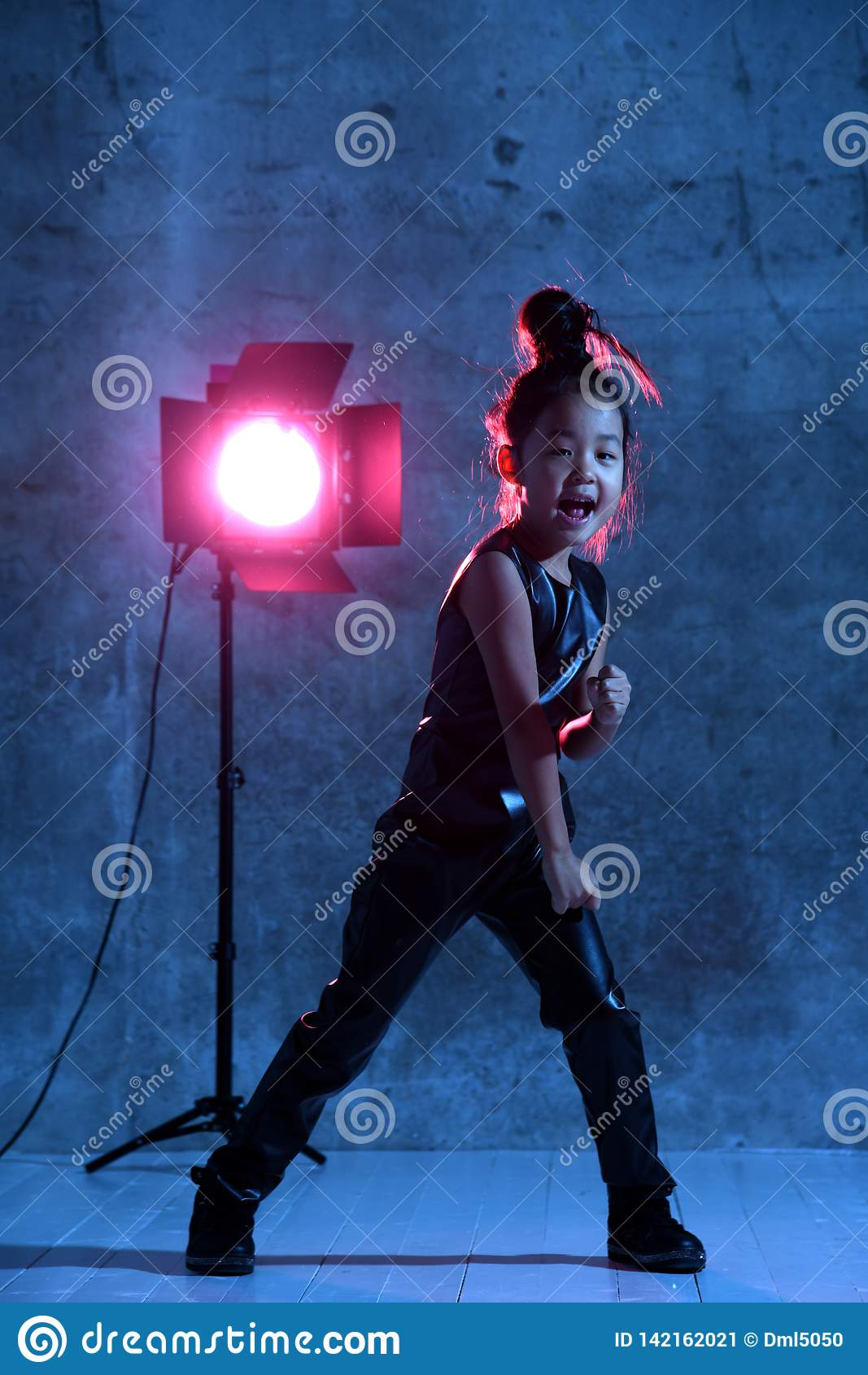 Το υψηλό ασιατικό πρότυπο κορίτσι μόδας με το επίκεντρο στούντιο ζωηρόχρωμο αποτελεί Η διάτρηση και φωνάζει