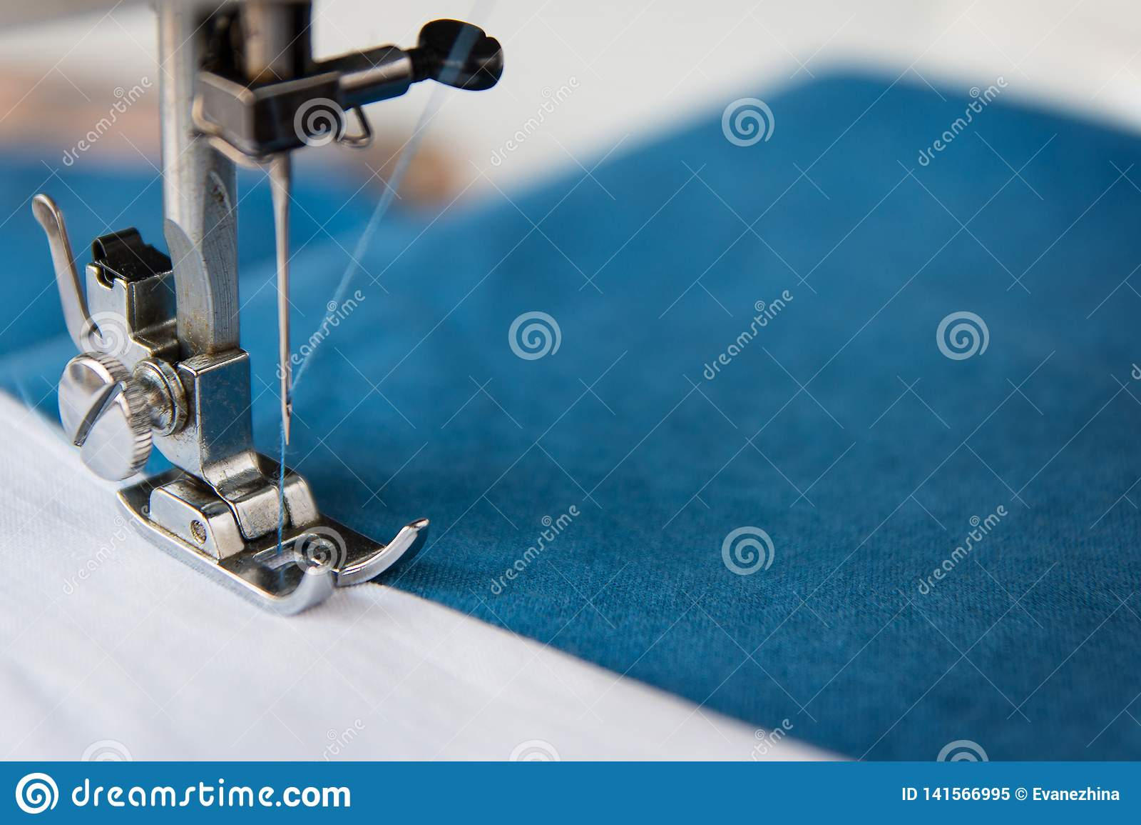 Το πόδι της ράβοντας μηχανής με μια βελόνα ράβει το μπλε ύφασμα