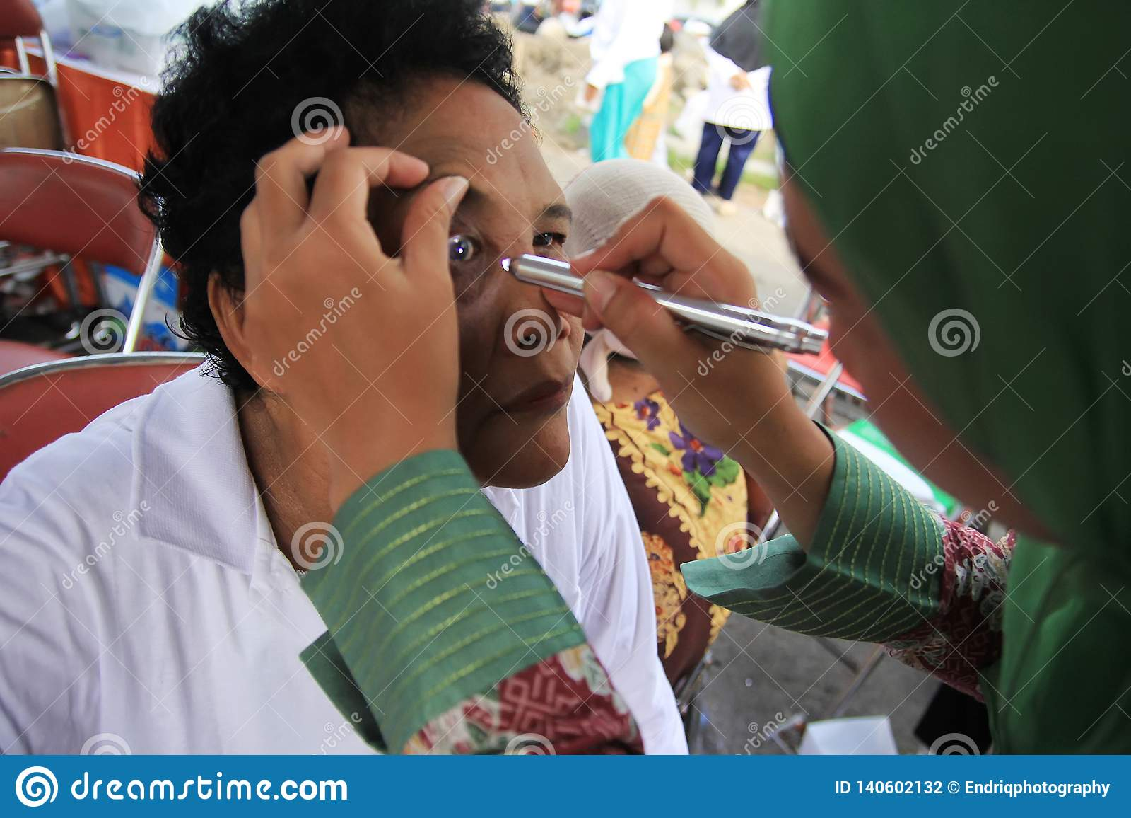 Το Surabaya Ινδονησία, μπορεί 21, το 2014 ένας εργαζόμενος στον ιατρικό κλάδο ελέγχει τα μάτια του ασθενή