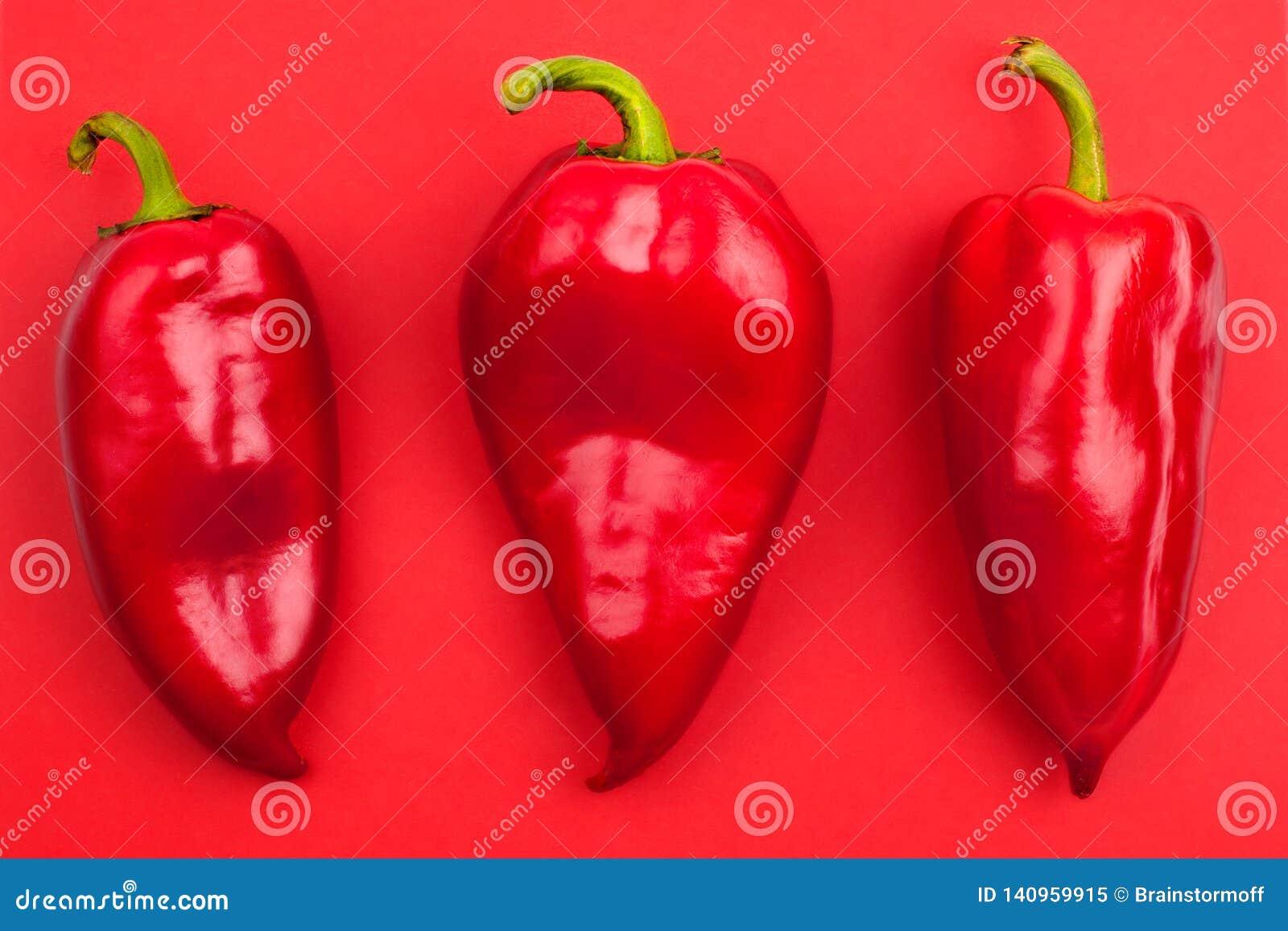 Τρία φωτεινά μεγάλα κόκκινα πιπέρια κουδουνιών με οι ουρές στην κόκκινη κινηματογράφηση σε πρώτο πλάνο άποψης υποβάθρου τοπ