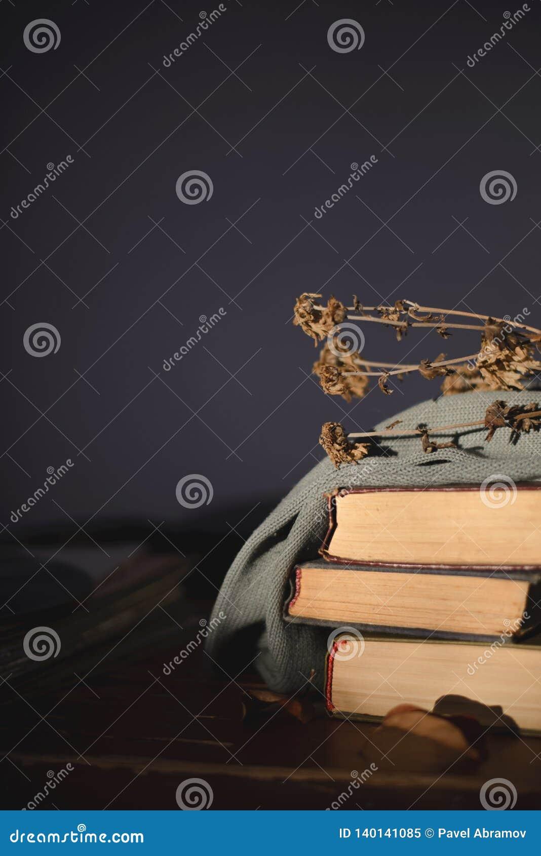 Τρία παλαιά βιβλία που καλύπτονται με ένα ύφασμα με το ψέμα στον πίνακα ένα ξηρό λουλούδι στην κορυφή
