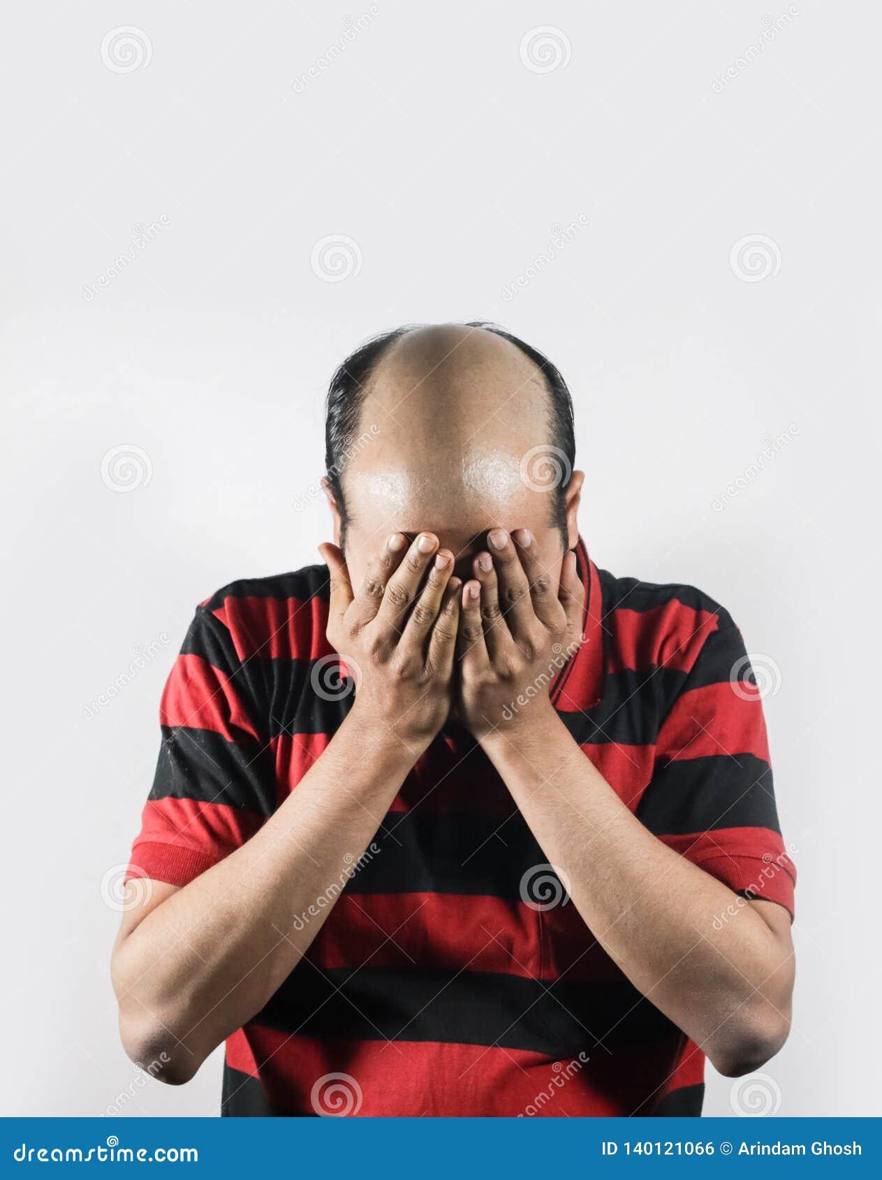 Φαλακρό άτομο που καλύπτει το πρόσωπό του στην ντροπή στο άσπρο υπόβαθρο με το διάστημα για το κείμενο