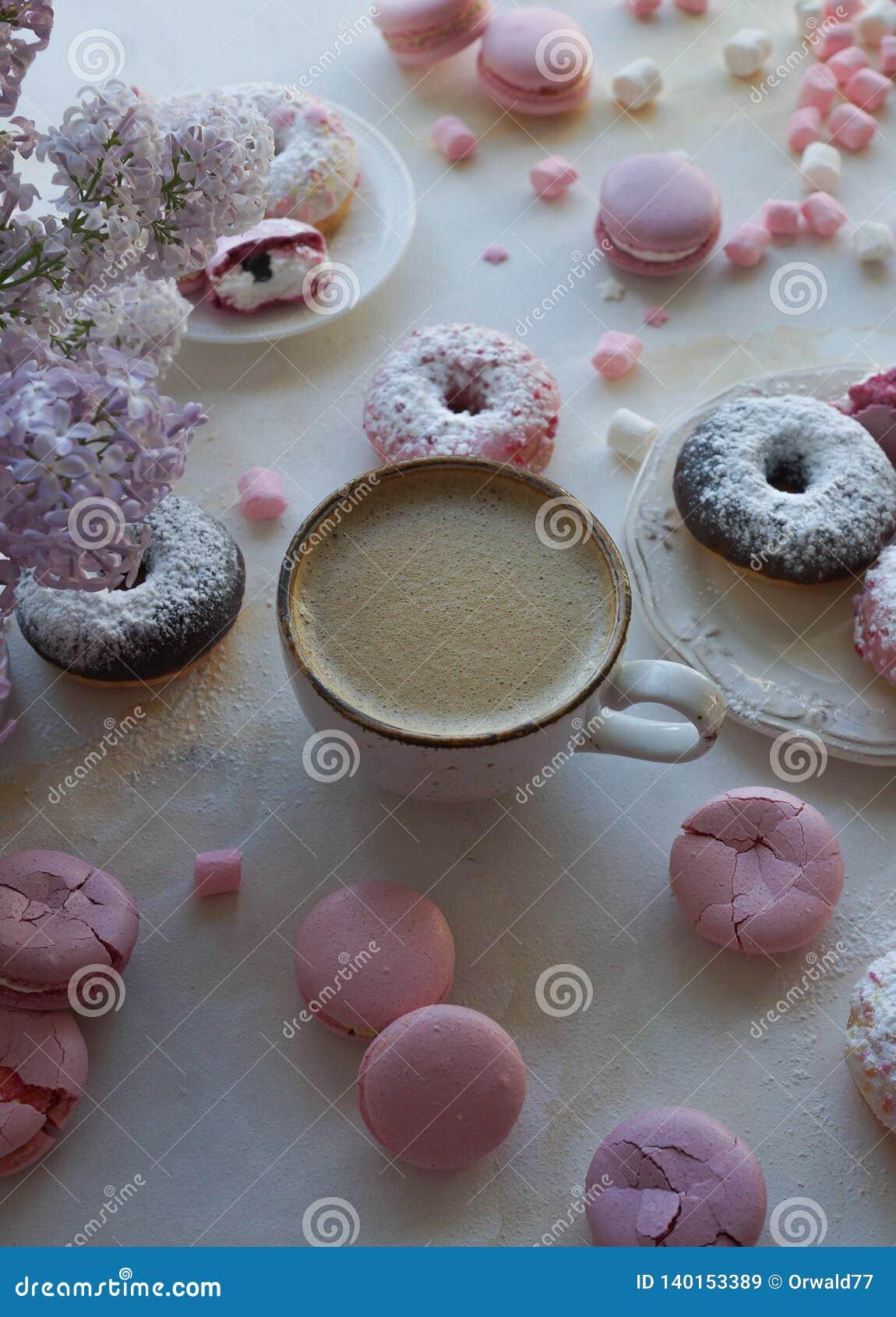 Φλυτζάνι του cappuccino, των φρέσκων ζωηρόχρωμων donuts, της φράουλας macarons και της ανθοδέσμης της πασχαλιάς στον άσπρο μαρμάρ