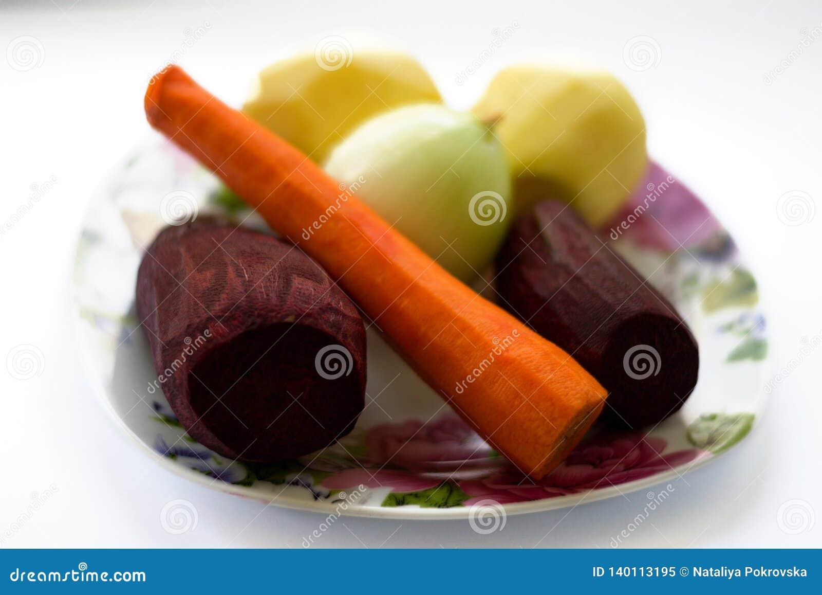Φρέσκα λαχανικά - τεύτλο, καρότο, πατάτα, κρεμμύδι στο πιάτο που απομονώνεται στο άσπρο υπόβαθρο Συστατικά που προετοιμάζονται γι