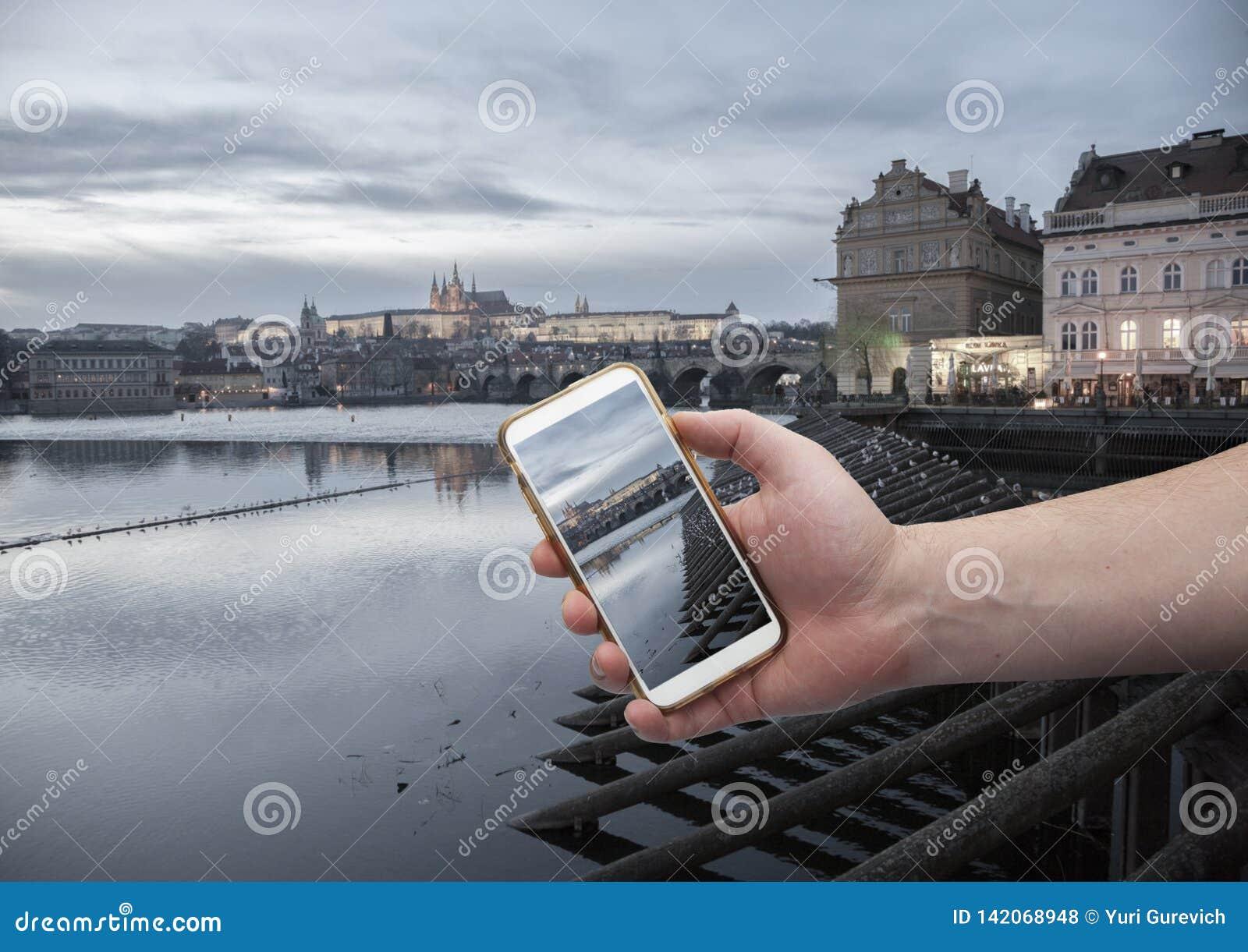 Φυσική άποψη του ιστορικού κέντρου Πράγα, γέφυρα του Charles και κτήρια του παλαιού πόλης χεριού με ένα smartphone, στην οθόνη το