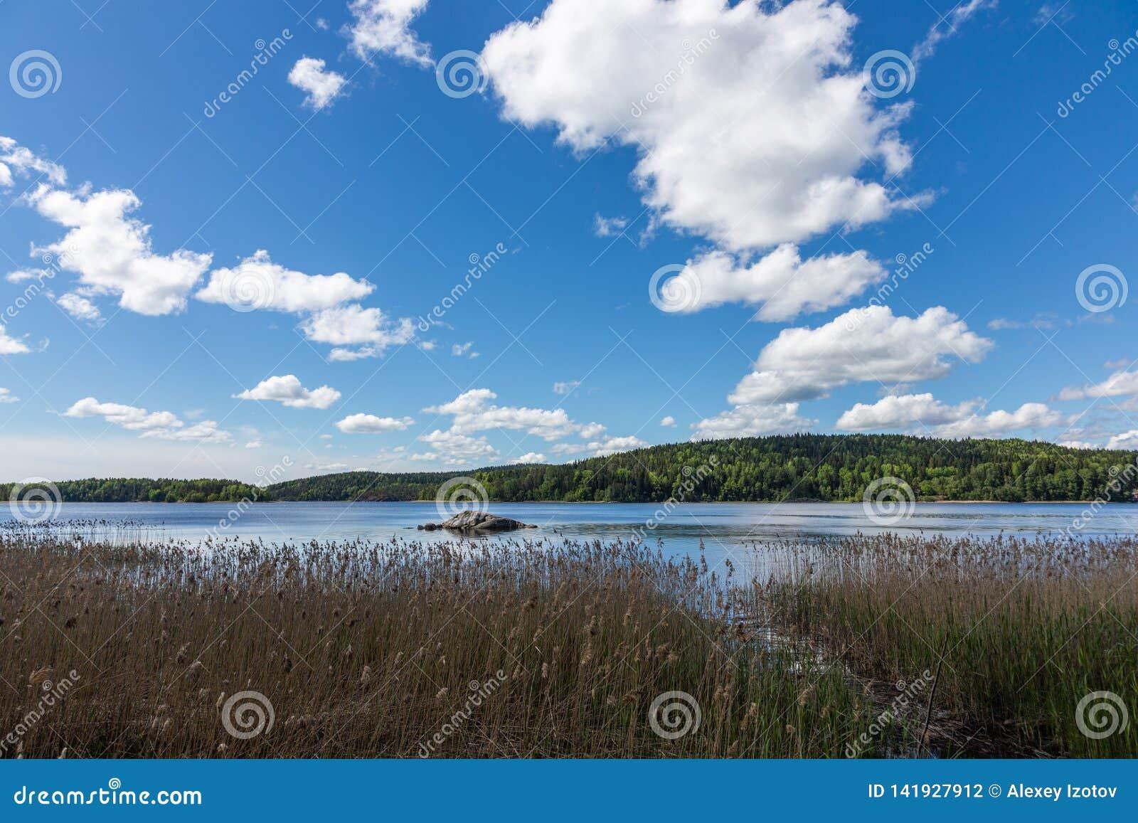 Φυσική άποψη του σαμάνου πετρών στη λίμνη Tulmozero κάτω από έναν μπλε ουρανό με τα σύννεφα, Καρελία Ρωσία
