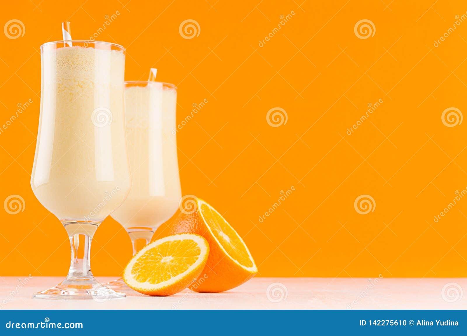 Φωτεινά πορτοκάλια milkshakes με τα εσπεριδοειδή φετών, το ριγωτό άχυρο στον άσπρο ξύλινο πίνακα και το ζωηρόχρωμο πορτοκαλή τοίχ