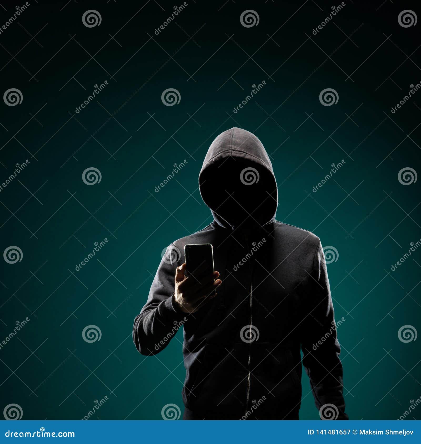 Χάκερ υπολογιστών στο hoodie Κρυμμένο σκοτεινό πρόσωπο Κλέφτης στοιχείων, απάτη Διαδικτύου, darknet και cyber έννοια ασφάλειας