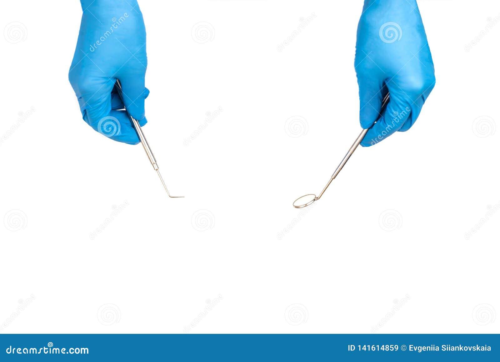 Χέρια οδοντιάτρου τα εργαλεία που απομονώνονται με στο λευκό