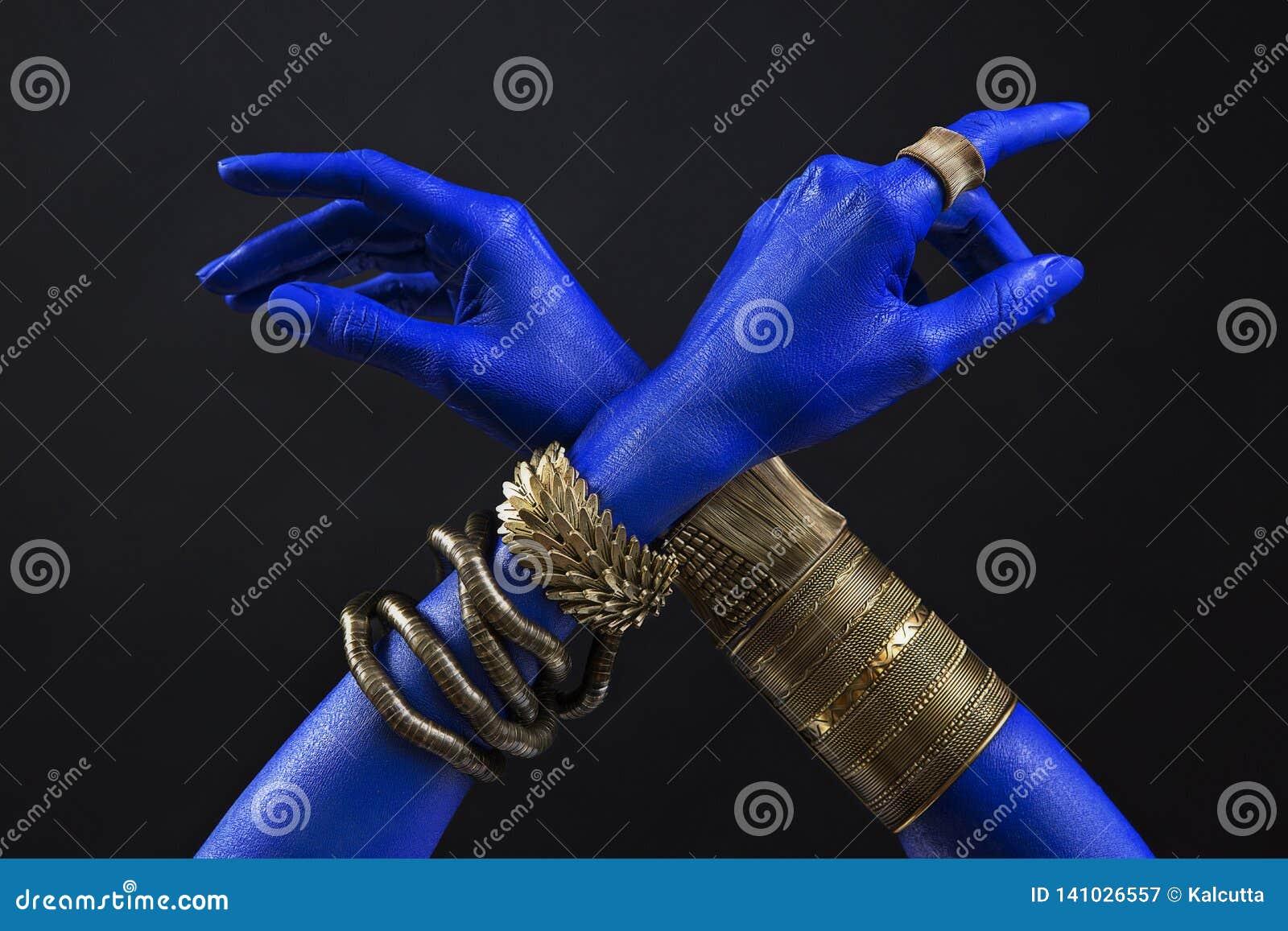 Χέρια της μπλε γυναίκας με το ινδικό χρυσό κόσμημα Ασιατικά βραχιόλια σε ετοιμότητα Χρυσά εξαρτήματα κοσμήματος και πολυτέλειας σ