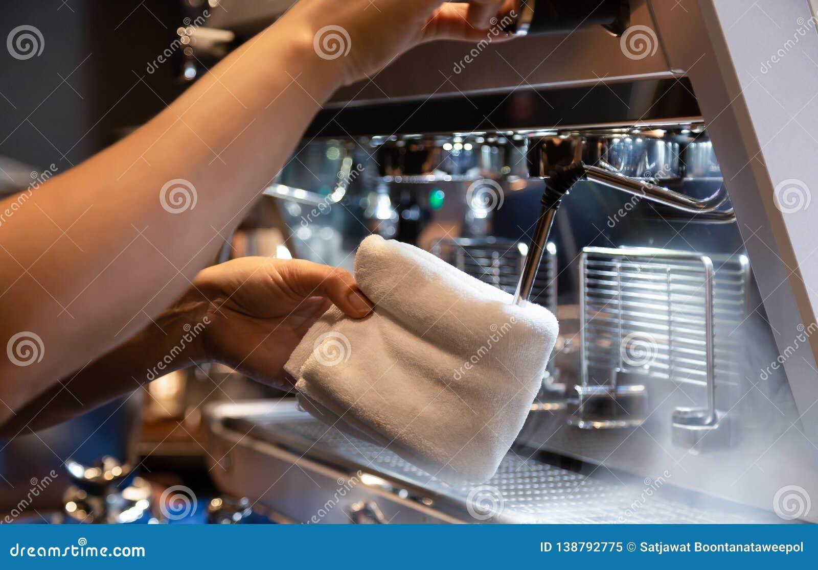 Χέρι του καθαρίζοντας γάλακτος barista frother της μηχανής καφέ για να είναι έτοιμος για να αφρίσει γάλακτος