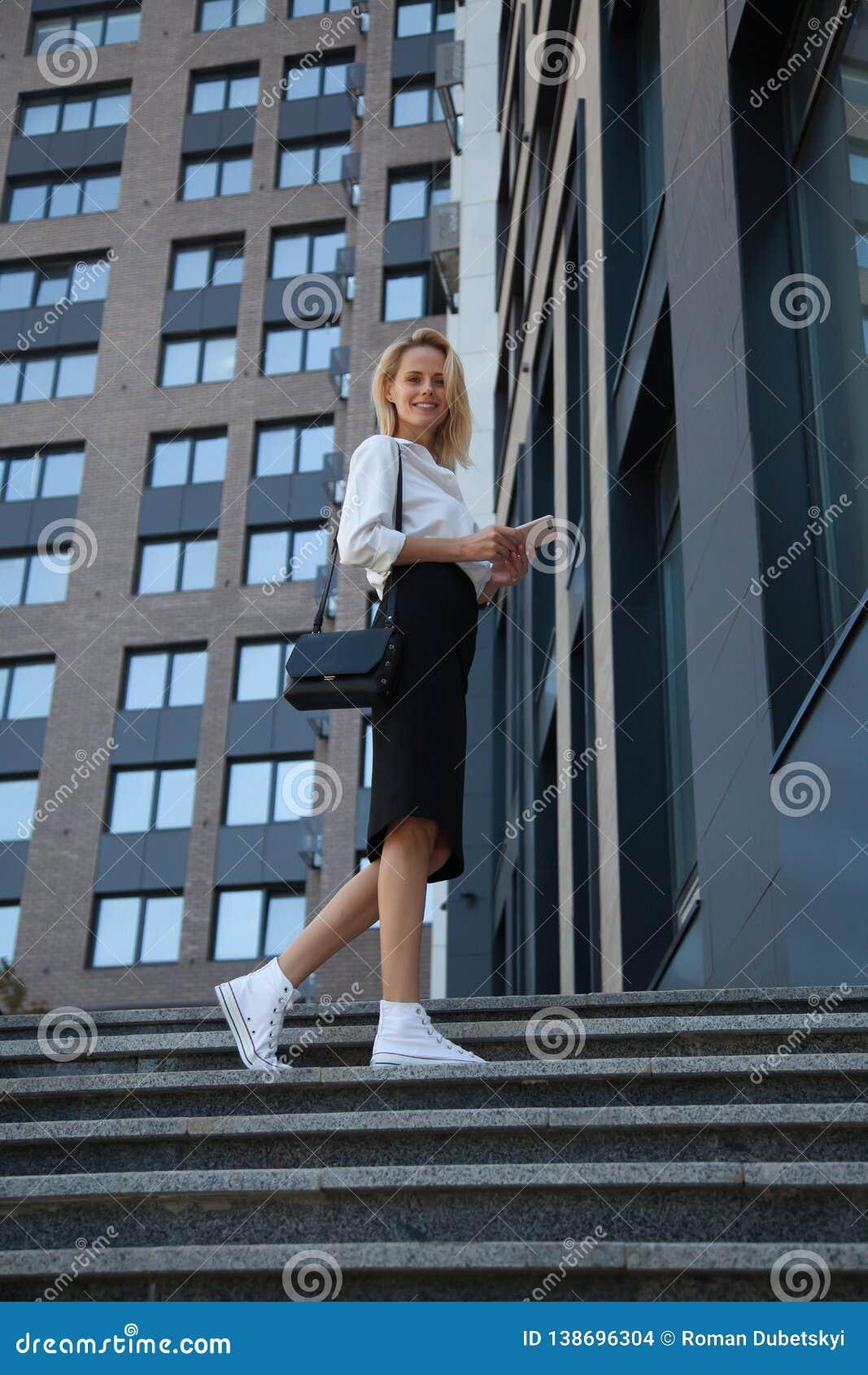 Χαμογελώντας επιχειρησιακή γυναίκα με το τηλέφωνο τσαντών και κυττάρων ενάντια στο κτίριο γραφείων