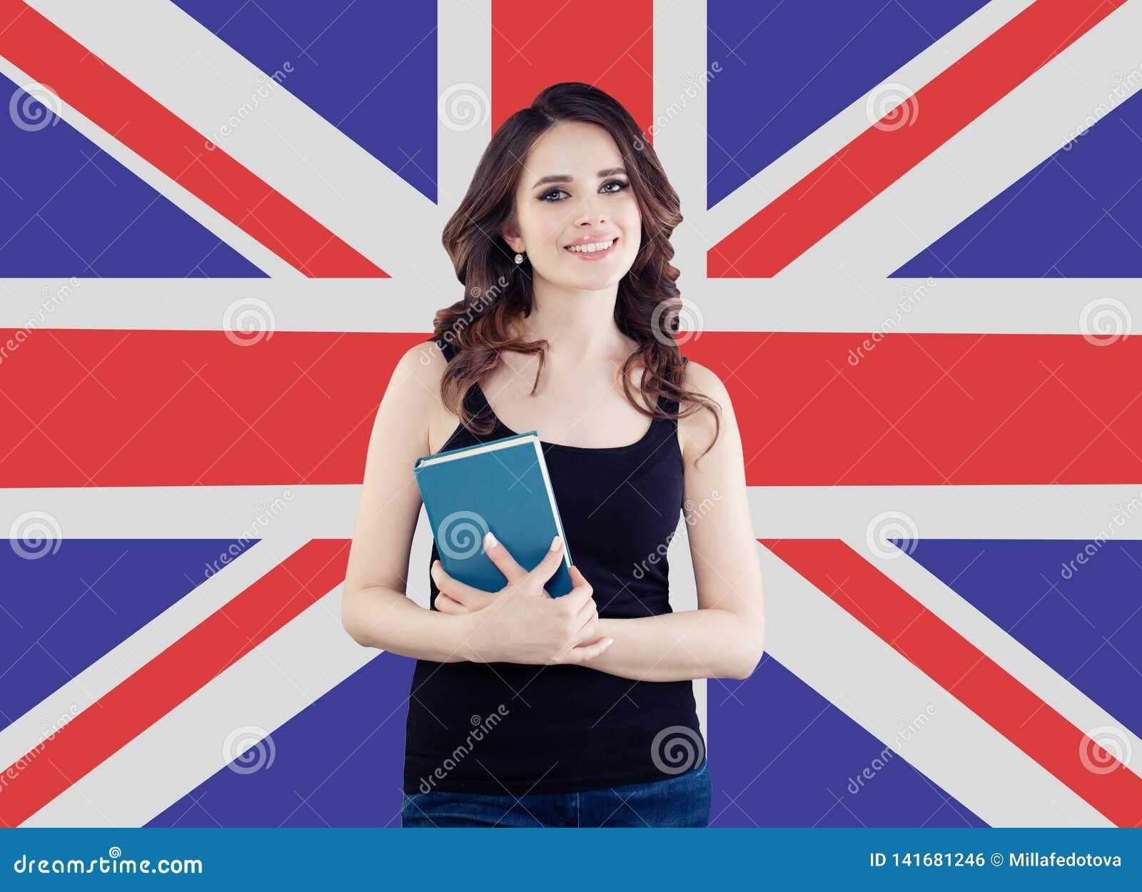 Χαμογελώντας κορίτσι στο υπόβαθρο βρετανικών σημαιών Αρκετά εύθυμη αγγλική γλώσσα εκμάθησης γυναικών και ταξιδεύω στο Ηνωμένο Βασ