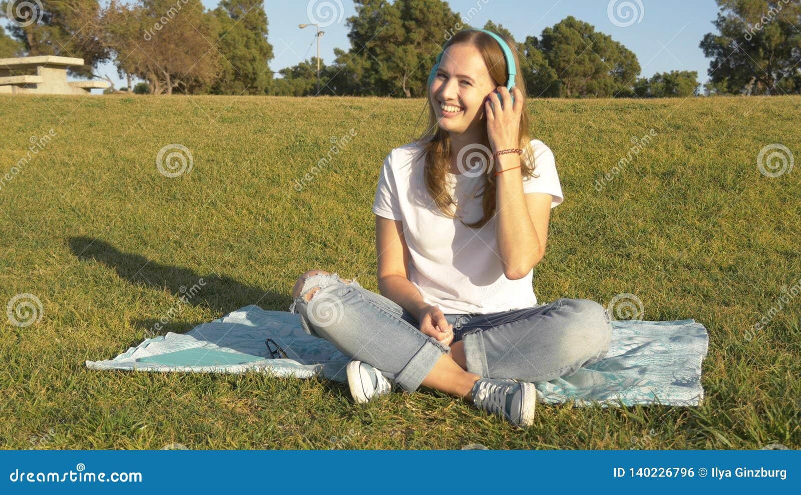 Χαμογελώντας νέα γυναίκα με το ασύρματο κάθισμα ακουστικών στην πράσινη χλόη