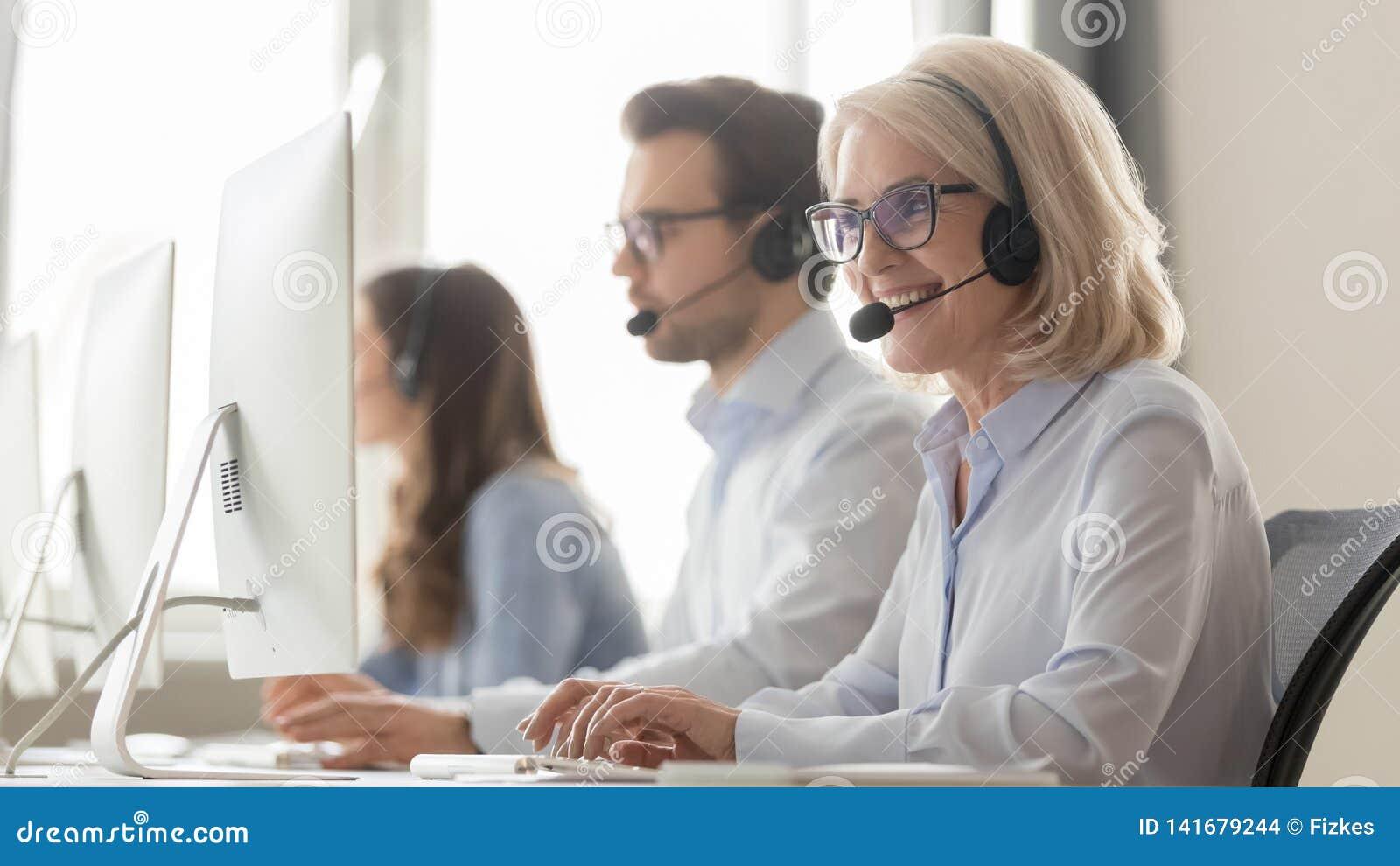 Χαμογελώντας παλαιός θηλυκός πράκτορας τηλεφωνικών κέντρων στο συμβουλευτικό πελάτη κασκών
