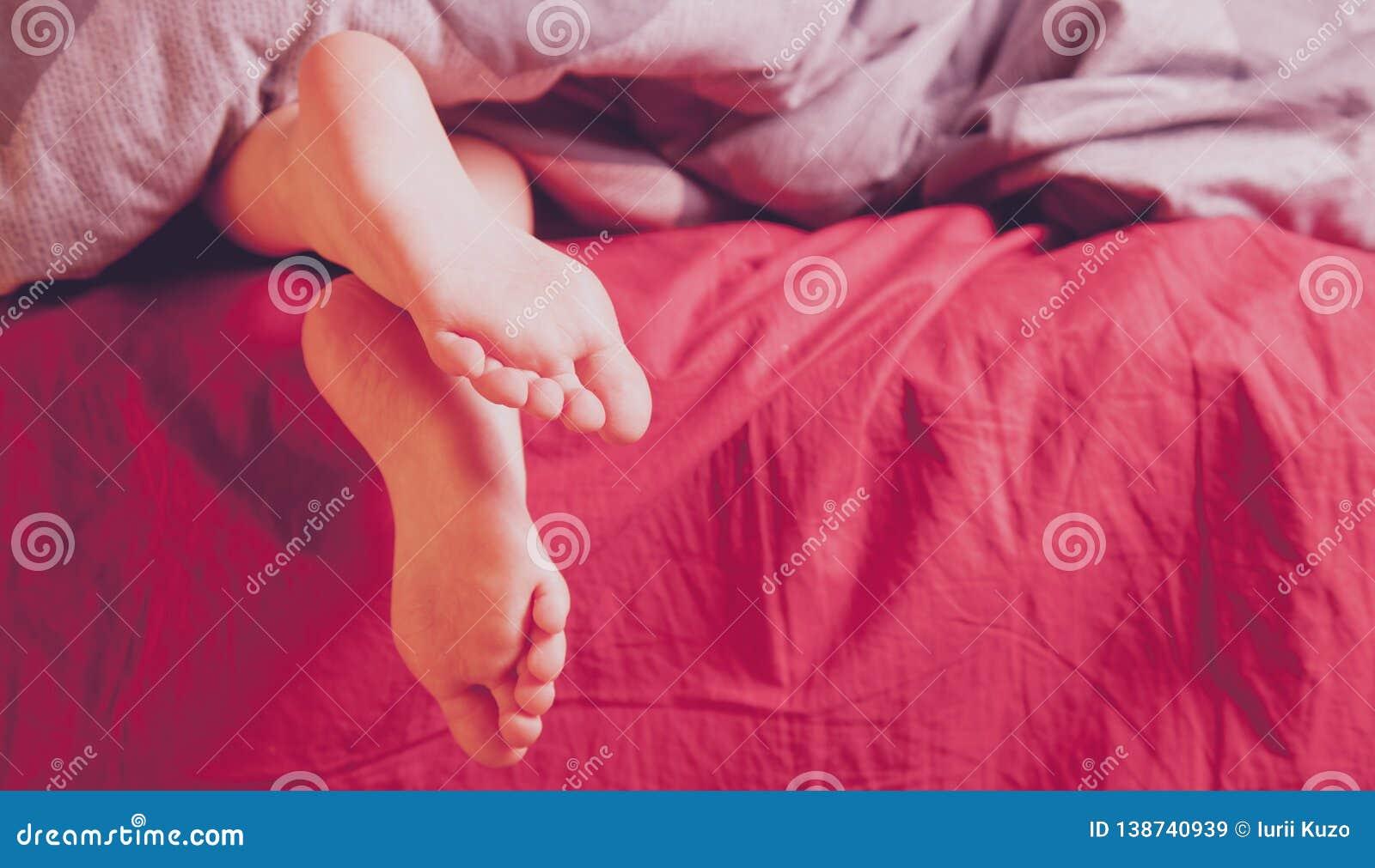 Χαριτωμένος λίγος ύπνος κοριτσιών παιδιών στο κρεβάτι στο σπίτι Πόδια κάτω από το κάλυμμα στο κρεβάτι της στην κρεβατοκάμαρα