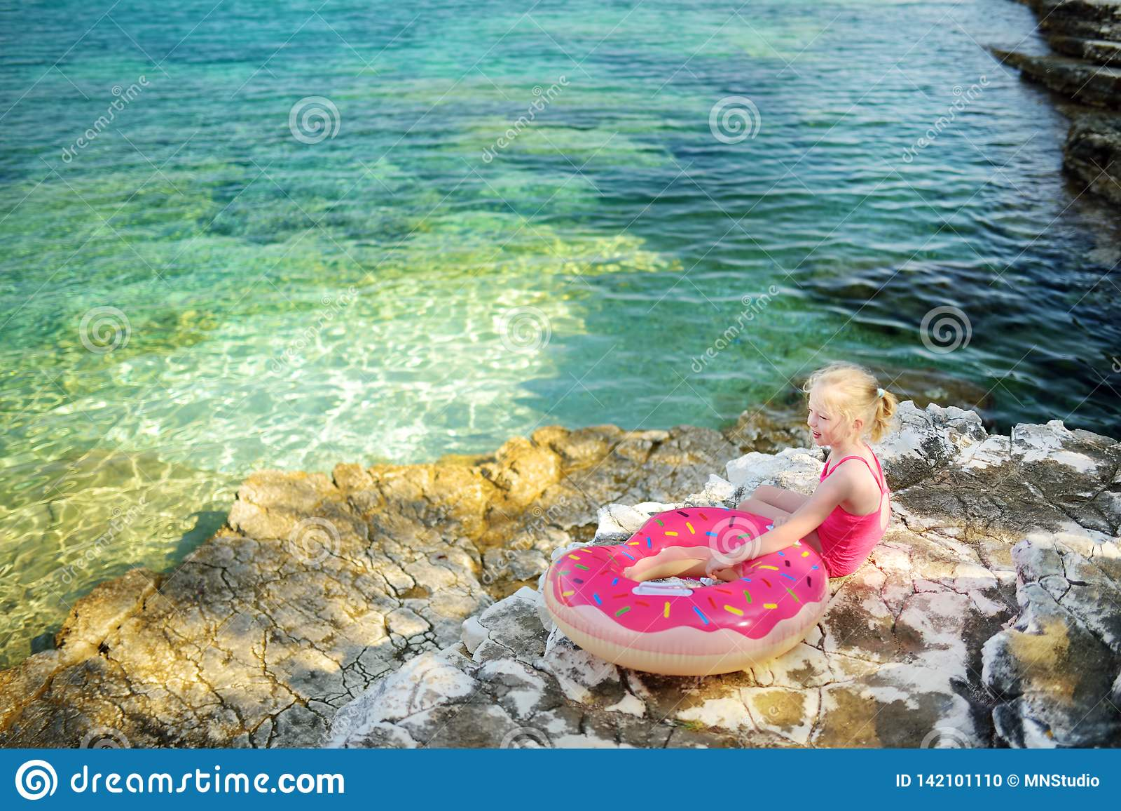 Χαριτωμένο μικρό κορίτσι που έχει τη διασκέδαση στην παραλία Emplisi, γραφική πετρώδης παραλία σε έναν απομονωμένο κόλπο, με τα σ