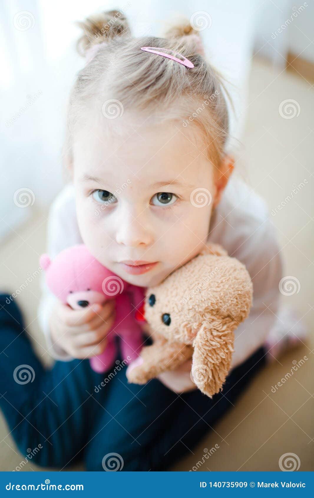 Χαριτωμένο μικρό κορίτσι που κρατά δύο teddy αρκούδες - που στρέφονται ελαφρώς στα μάτια της