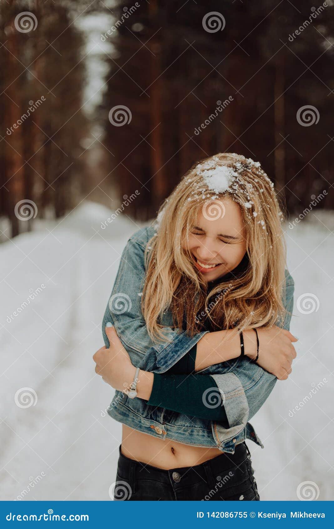 Χαριτωμένο νέο όμορφο πορτρέτο κοριτσιών χαμόγελου στο χειμερινό χιονώδες δάσος με το χιόνι στην τρίχα του