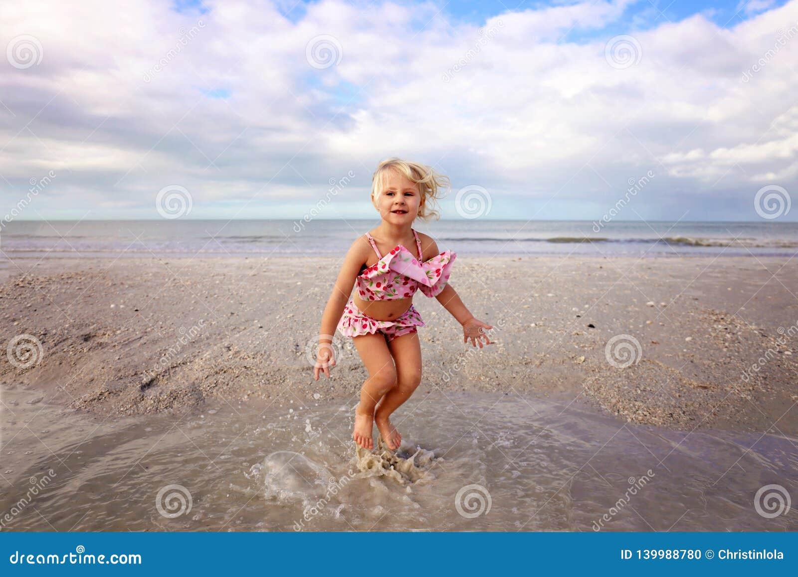 Χαριτωμένο παιδάκι που καταβρέχει και που παίζει στο νερό στην παραλία από τον ωκεανό