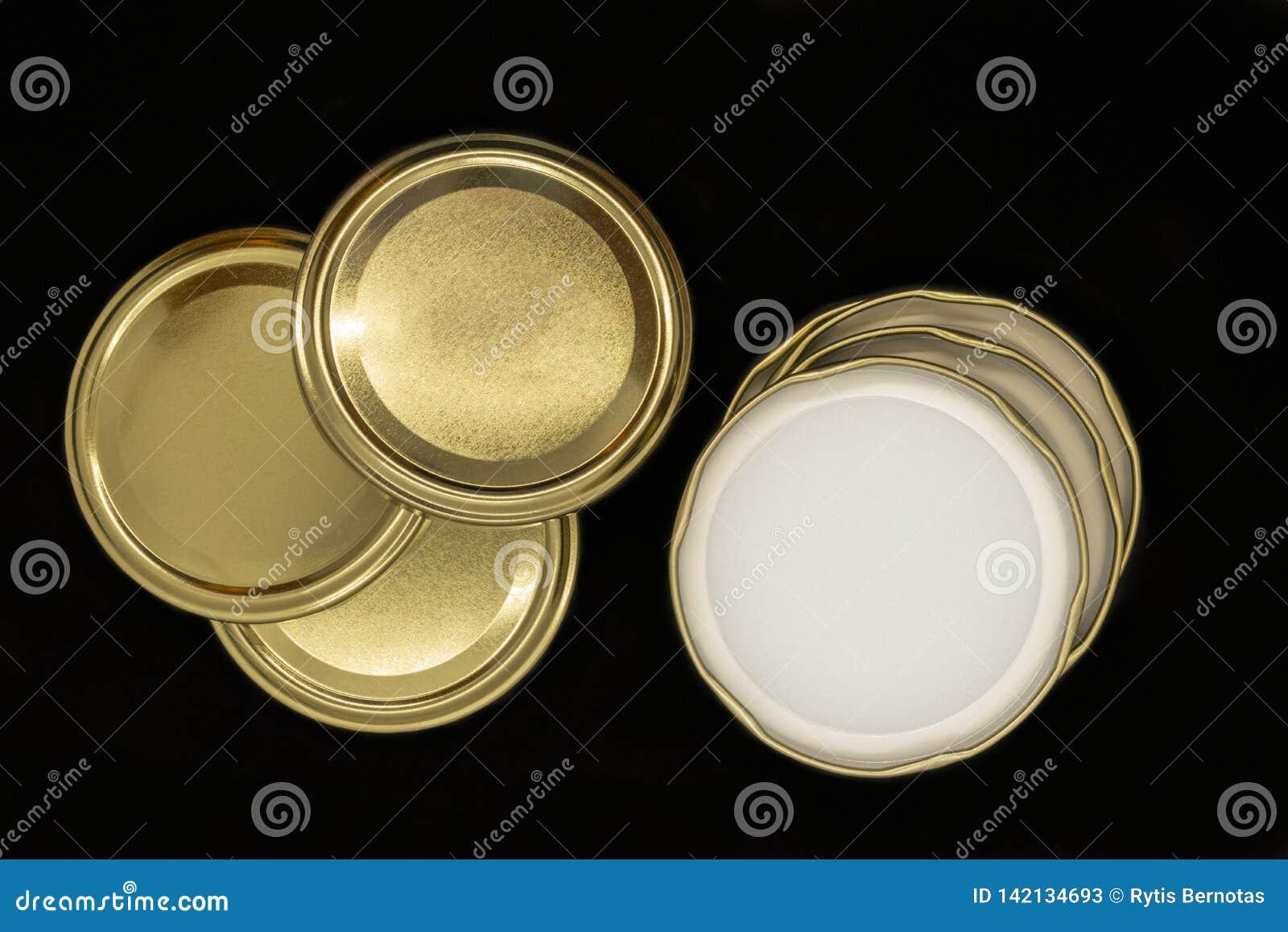 Χρυσά καπάκια βάζων που απομονώνονται στο μαύρο υπόβαθρο