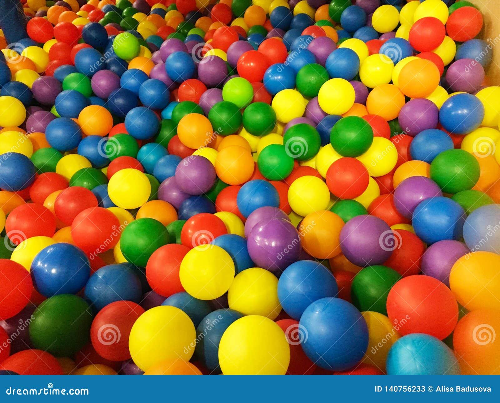 Χρωματισμένες πλαστικές σφαίρες στην ομάδα του δωματίου παιχνιδιών Πισίνα για τη διασκέδαση και πηδώντας στις χρωματισμένες πλαστ