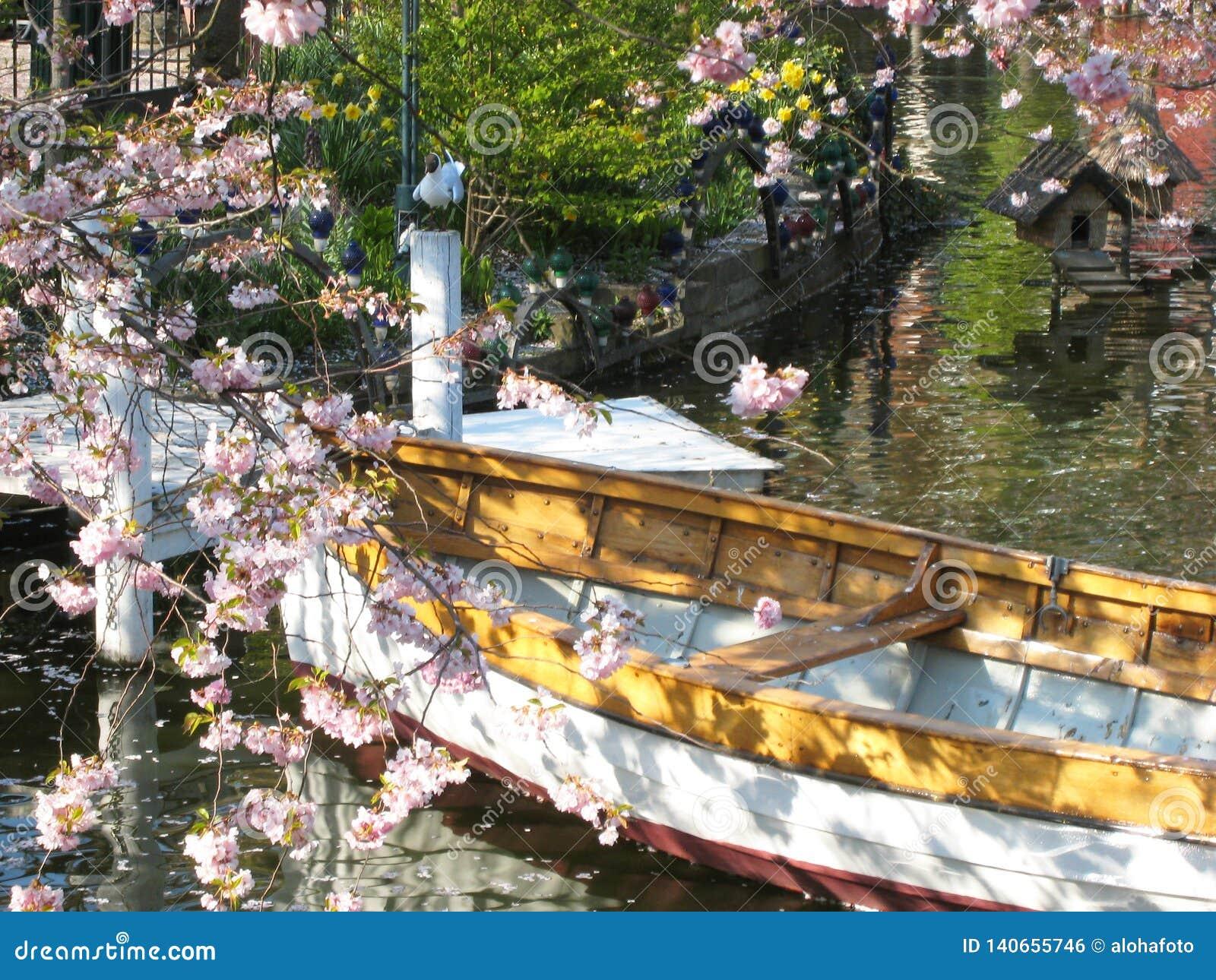 Υπέροχα η άποψη μιας ξύλινης βάρκας στην Κοπεγχάγη στη Δανία που περιβάλλεται θαλασσίως †‹â€ ‹ανθίζει σε μια μικρή λίμνη