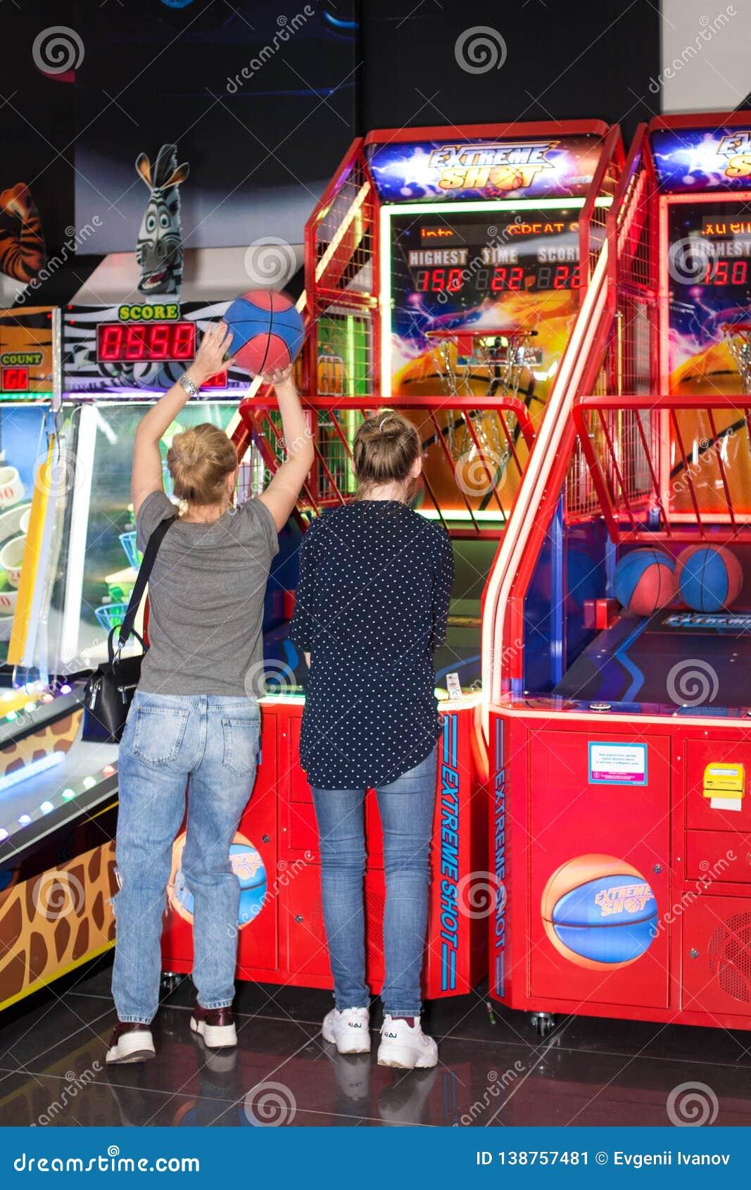 Παιχνίδι παιδιών και ενηλίκων στα μηχανήματα τυχερών παιχνιδιών με κέρματα, έλξη στο εμπορικό κέντρο Οι οικογένειες με τα παιδιά