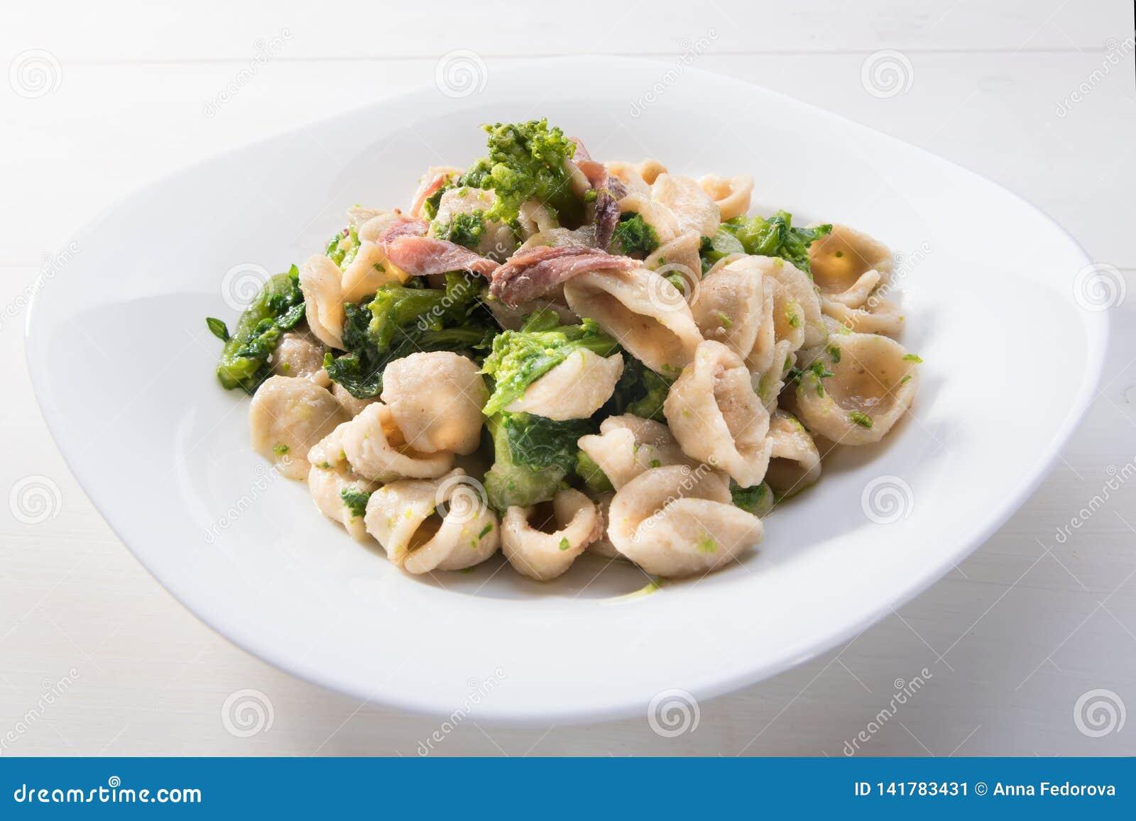 Παραδοσιακό πιάτο των ζυμαρικών Orecchiette περιοχών Apulia με τα πράσινα κραμβών και τις αλατισμένες αντσούγιες, τοπ άποψη, άσπρ