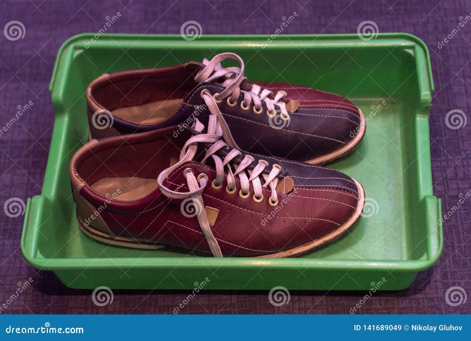 Πολύχρωμα παπούτσια δέρματος με τις δαντέλλες, ένα ζευγάρι, για το παιχνίδι του μπόουλινγκ σε έναν πλαστικό δίσκο