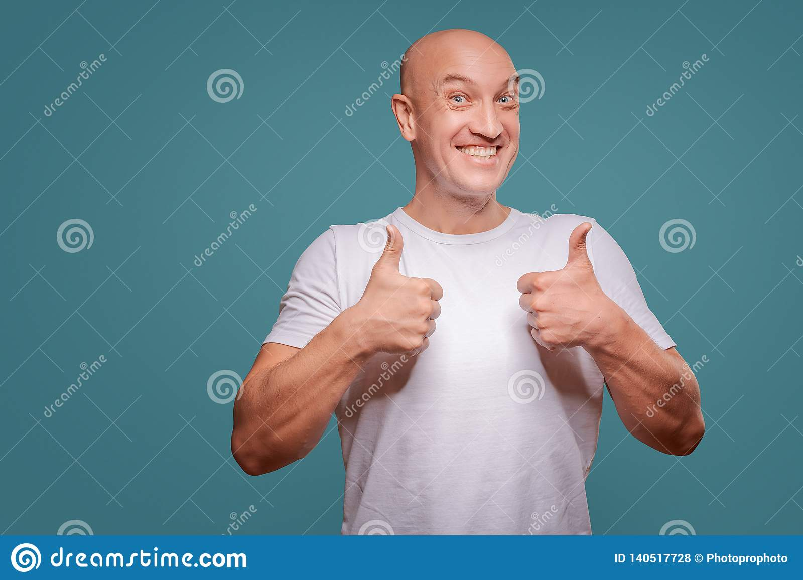 Πορτρέτο ενός εύθυμου ατόμου που παρουσιάζει εντάξει χειρονομία που απομονώνεται στο μπλε υπόβαθρο