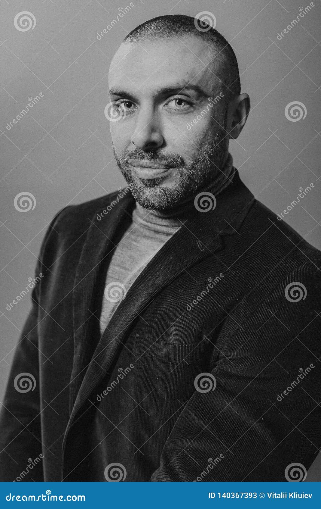 Πορτρέτο μόδας στούντιο σε μονοχρωματικό Το κομψό νέο όμορφο σοβαρό άτομο άνοιξε το σακάκι του