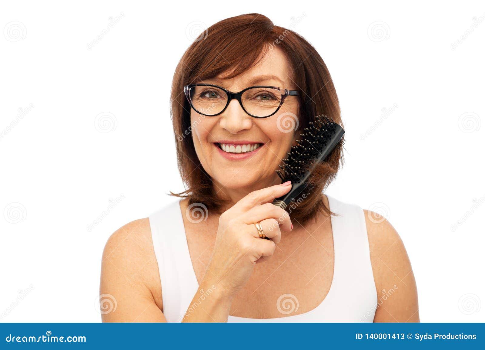 Πορτρέτο της ανώτερης γυναίκας στα γυαλιά που βουρτσίζουν την τρίχα