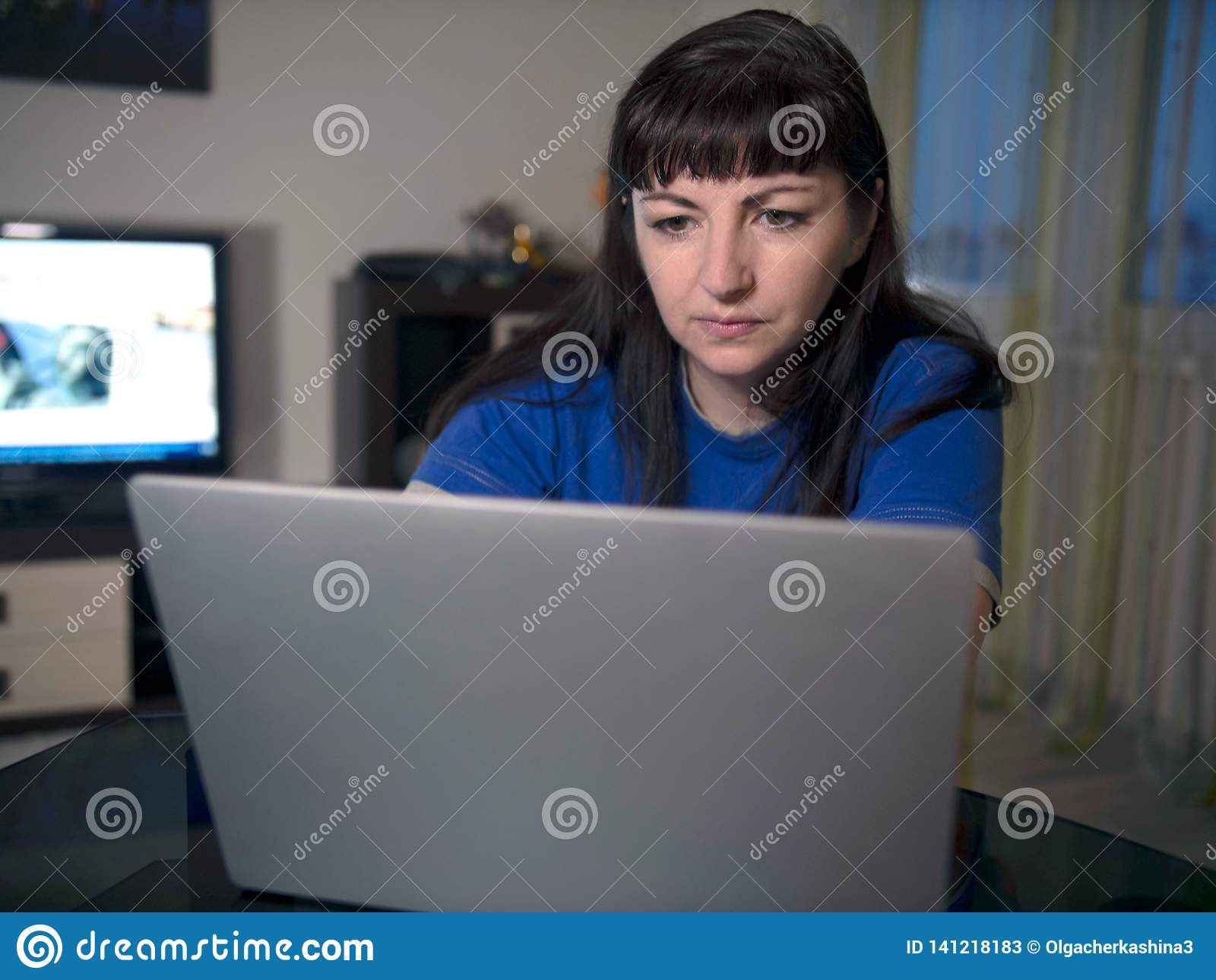 Πορτρέτο της νέας γυναίκας που εργάζεται στο lap-top στο σπίτι το βράδυ