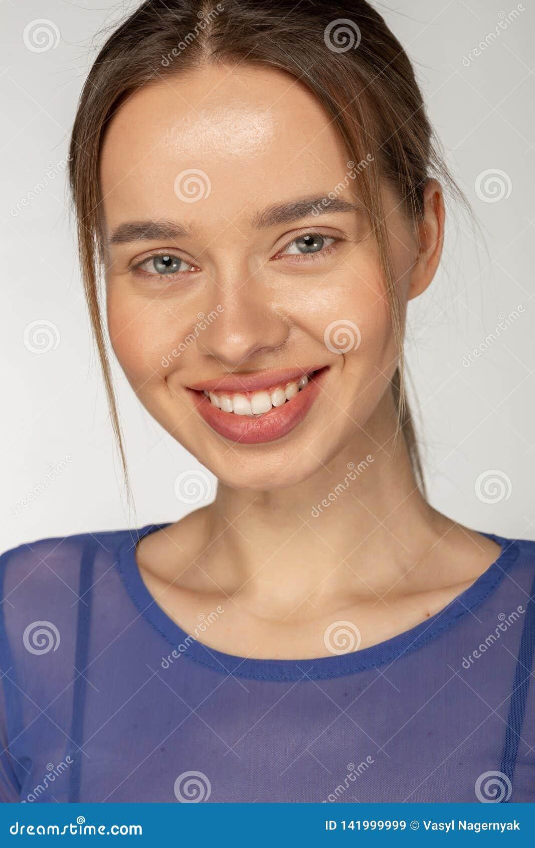 Πορτρέτο του νέου όμορφου χαριτωμένου εύθυμου χαμόγελου κοριτσιών στη κάμερα