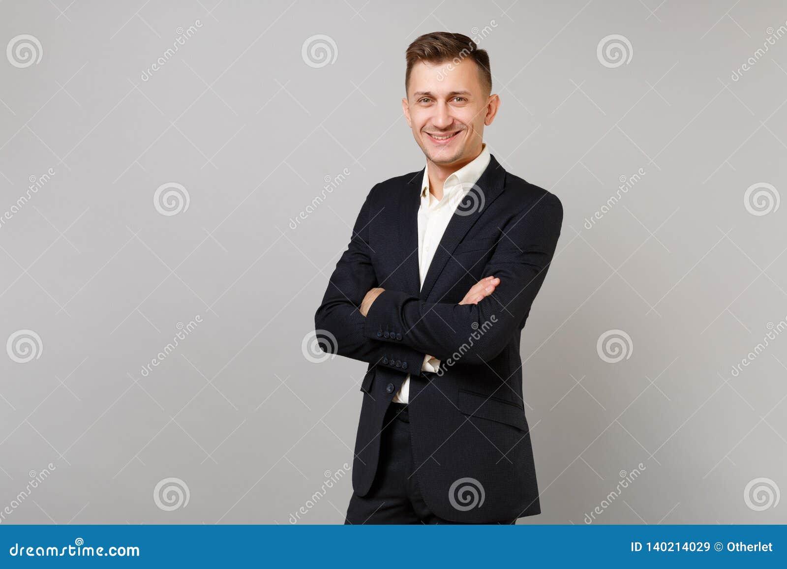 Πορτρέτο του χαμογελώντας νέου επιχειρησιακού ατόμου στα κλασικά μαύρα χέρια εκμετάλλευσης κοστουμιών και πουκάμισων που διπλώνον