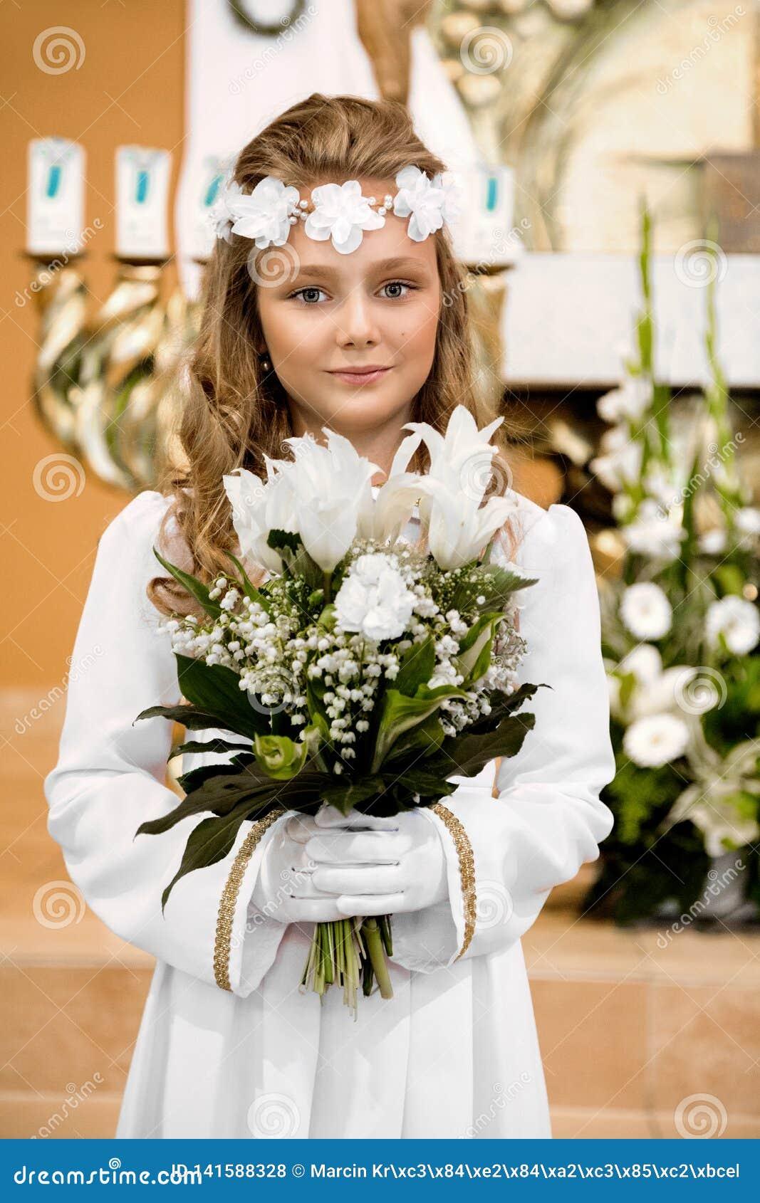 Πορτρέτο του χαριτωμένου μικρού κοριτσιού στο άσπρο φόρεμα και του στεφανιού στην πρώτη ιερή πύλη εκκλησιών υποβάθρου κοινωνίας