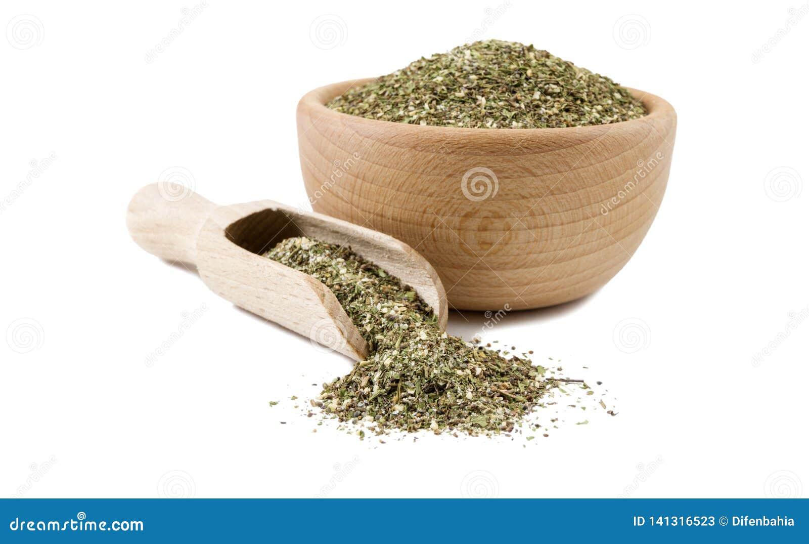 Πράσινο αλμυρό μίγμα ή Chubritsa στο ξύλινο κύπελλο και σέσουλα που απομονώνεται στο άσπρο υπόβαθρο Καρυκεύματα και συστατικά τρο