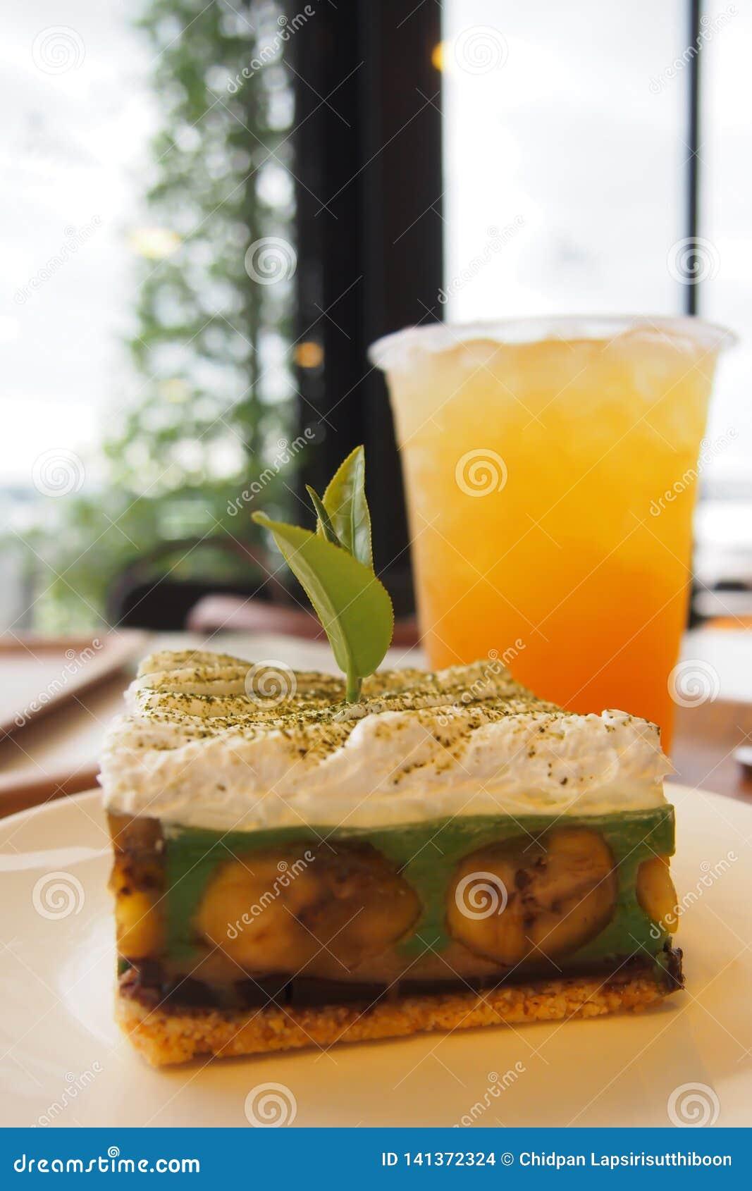 Πράσινο τσάι Banoffee, ένα υπέροχα διακοσμημένο αρτοποιείο σε ένα άσπρο πιάτο και τσάι πάγου λεμονιών στον πίνακα σε ένα κατάστημ