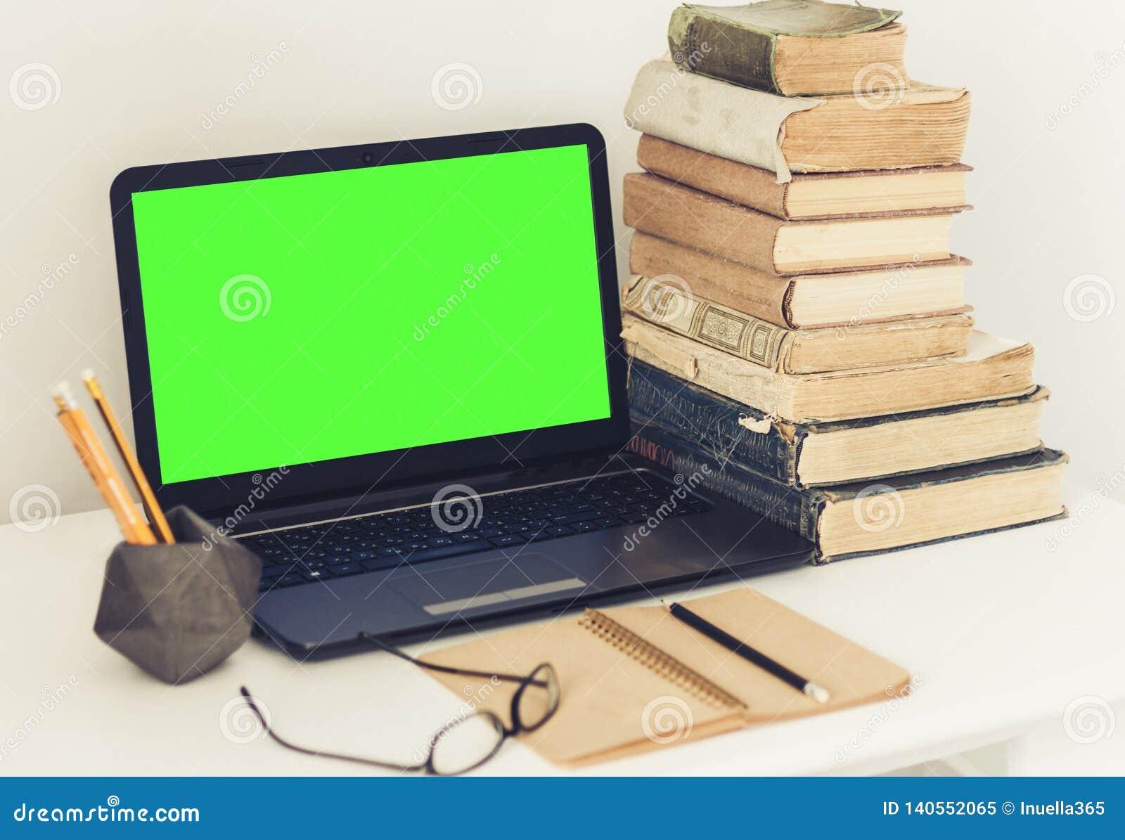 Πράσινο lap-top οθόνης, σωρός των παλαιών βιβλίων, σημειωματάριο και μολύβια στον άσπρο πίνακα, υπόβαθρο έννοιας γραφείων εκπαίδε