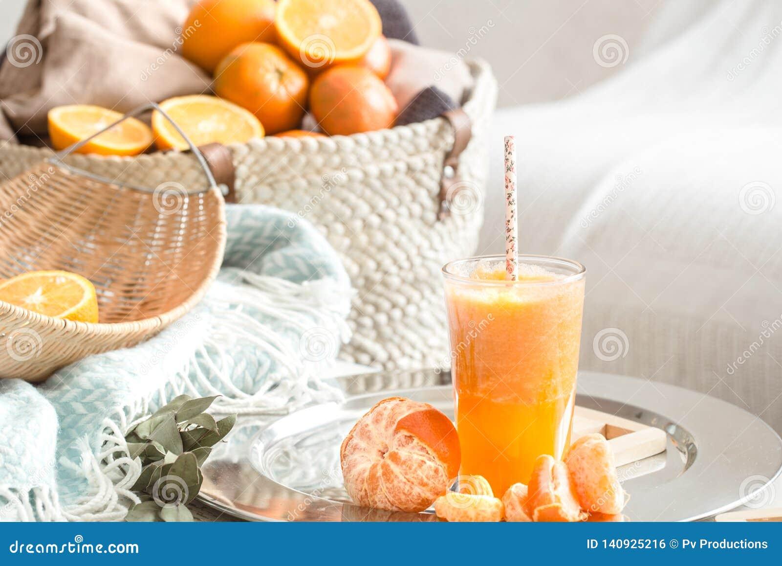 Πρόσφατα-αυξημένος οργανικός φρέσκος χυμός από πορτοκάλι στο εσωτερικό του σπιτιού, με ένα τυρκουάζ κάλυμμα και ένα καλάθι των φρ