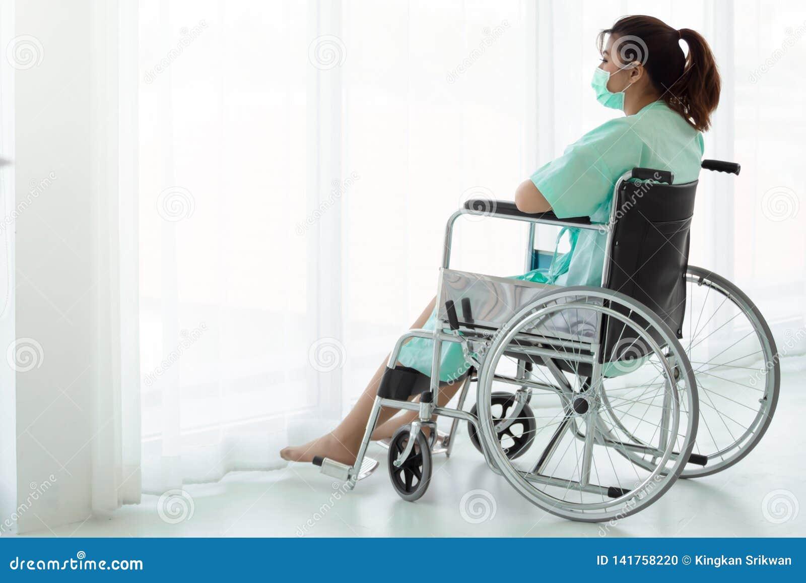 Азиатская женщина сидя на кресло-коляске смотря вне окна