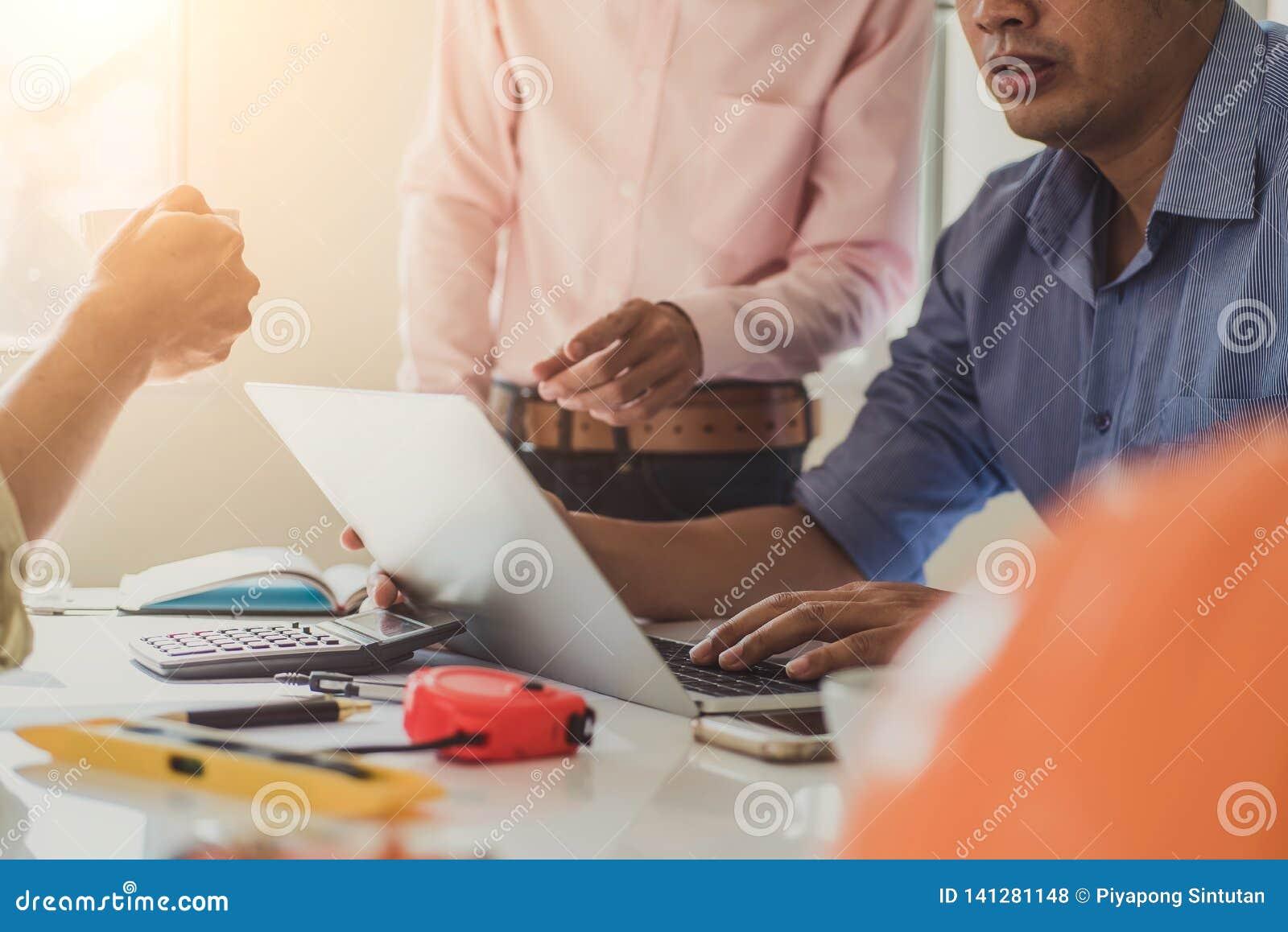 Азиатские бизнесмены группового обсуждения архитектора на встрече светокопий конструкции планируют Инструменты инженерства констр