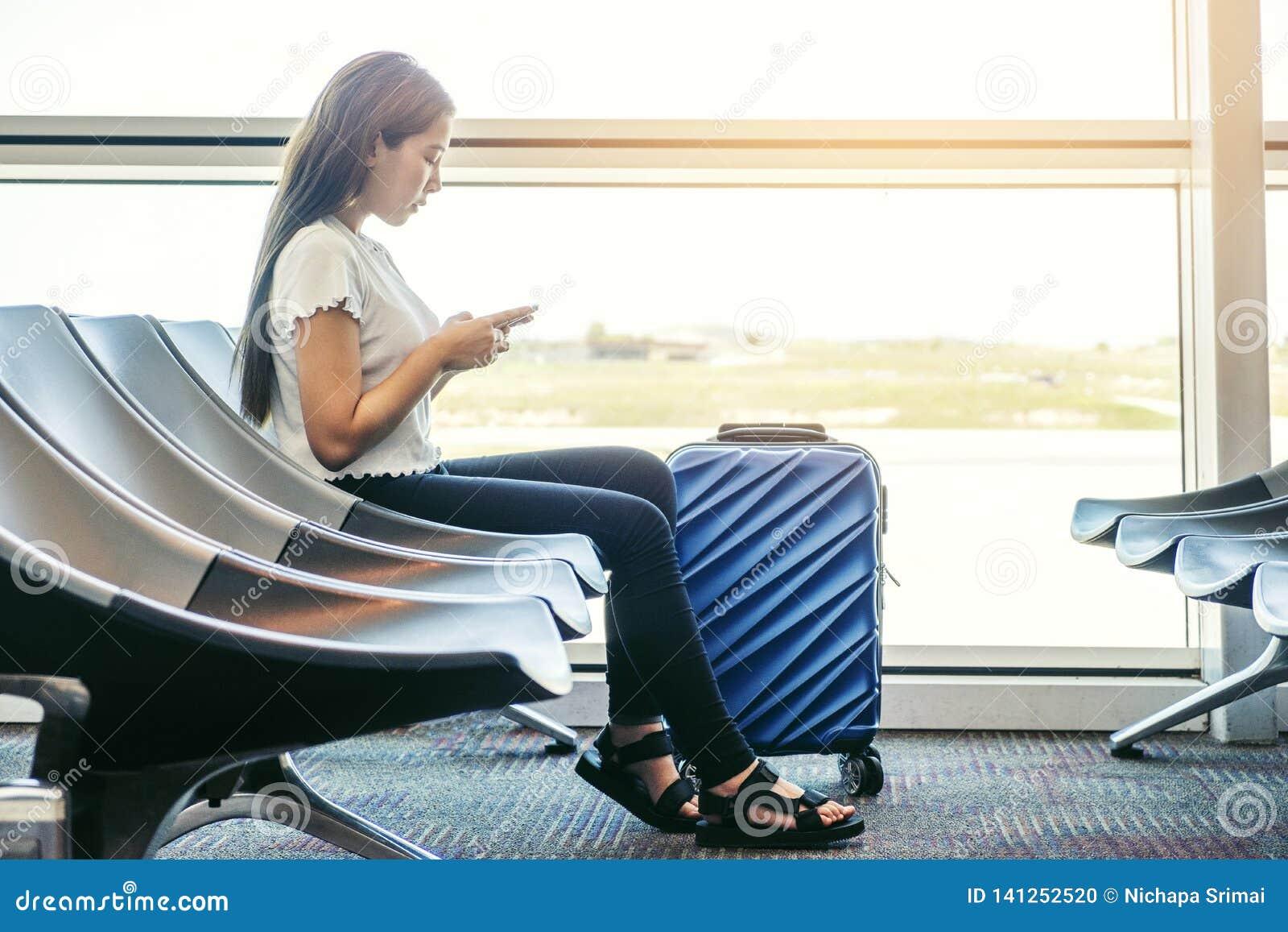 Азиатские женщины путешественника ища полет в смартфон на концепции перемещения крупного аэропорта