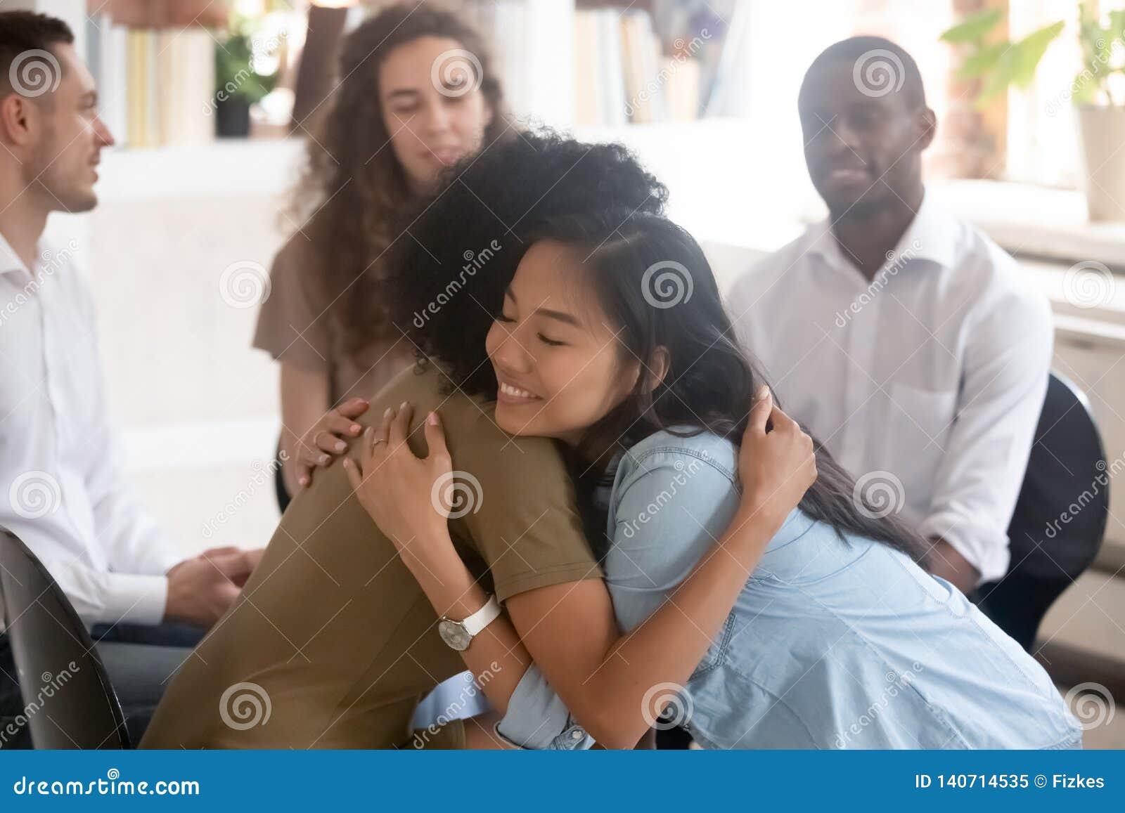 Азиатские и африканские женщины обнимая дающ психологическую поддержку во время терапии
